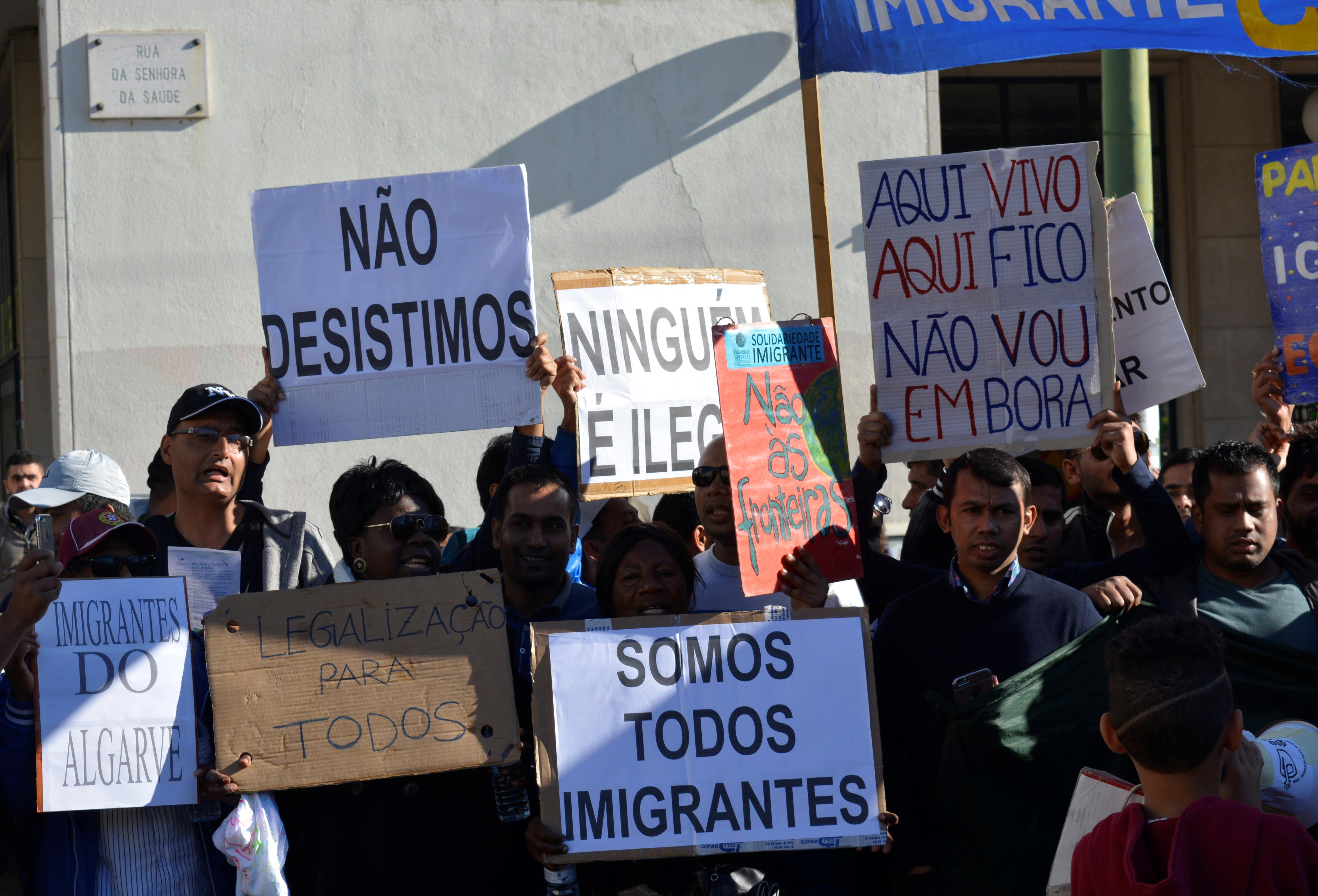 """Cartazes dos manifestantes, que incluem frases como """"Não desistimos"""", """"Somos todos imigrantes"""", """"Aqui vivo, aqui fico, não vou embora"""" e """"Legalização para todos""""."""