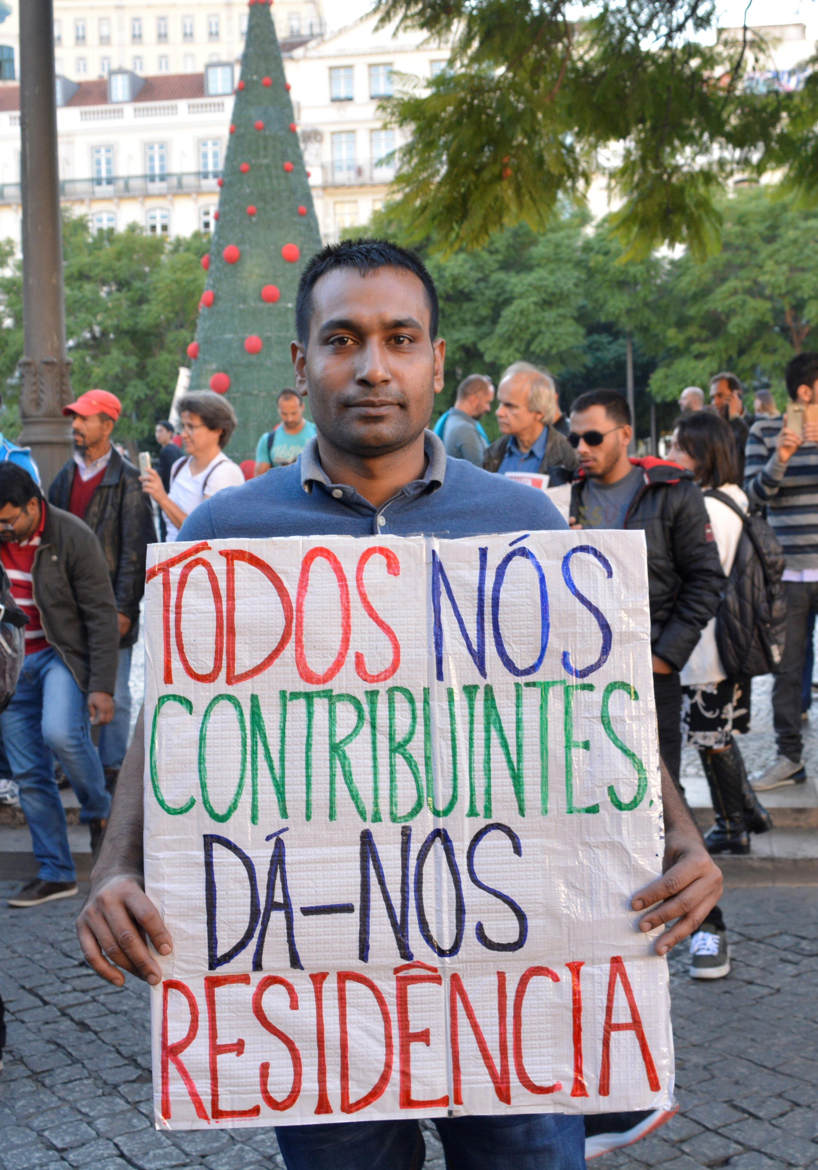 Manifestante imigrante com cartaz que apela a uma emissão de vistos de residência menos demorada.
