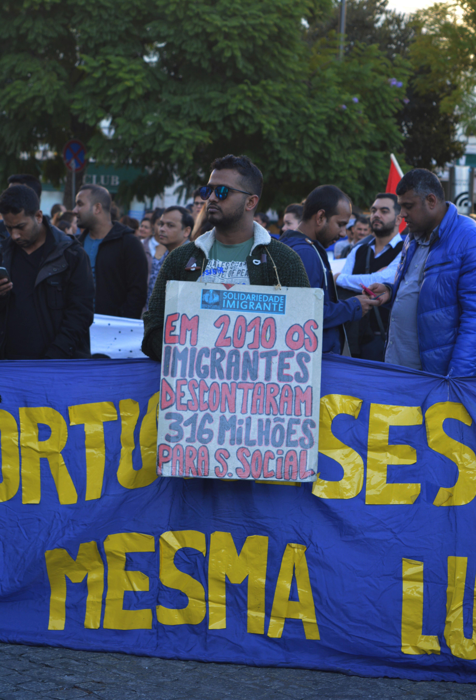 Manifestante com cartaz a reinvindicar os direitos dos imigrantes que trabalham em Portugal e descontam para a Segurança Social.