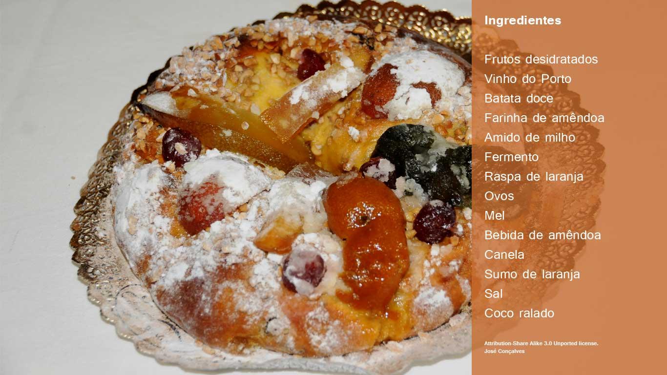 Preparação: 1-Corte os frutos desidratados em pequenos pedaços e coloque-os a macerar em vinho do Porto. 2-Coza a batata-doce descascada. Reduza-a a puré e deixe-a arrefecer. 3-Peneire a farinha de amêndoa e o amido de milho. Adicione o fermento e a raspa de laranja. Misture. 4-Numa tigela, com o puré de batata-doce, acrescente gradualmente os ovos, o mel e a bebida de amêndoa enquanto e vá mexendo. Tempere com canela, sumo de laranja e uma pitada de sal e envolva. 5-Aos poucos, junte o preparado de farinhas e misture todos os ingredientes. Por fim, acrescente as frutas desidratadas. 6-Cubra o recipiente com película anti-aderente e um pano e deixe repousar durante 90 minutos. Pré-aqueça o forno a 200º C. 7-Disponha a massa num tabuleiro com uma forma redonda forrada com uma folha de papel vegetal e faça um buraco ao centro. 8-Pincele o bolo com gema de ovo e decore distribuindo frutos secos. Leve o bolo ao forno a 180º C, durante 45 minutos, até ficar dourado. 9-Retire do forno, deixe arrefecer e polvilhe com coco ralado.