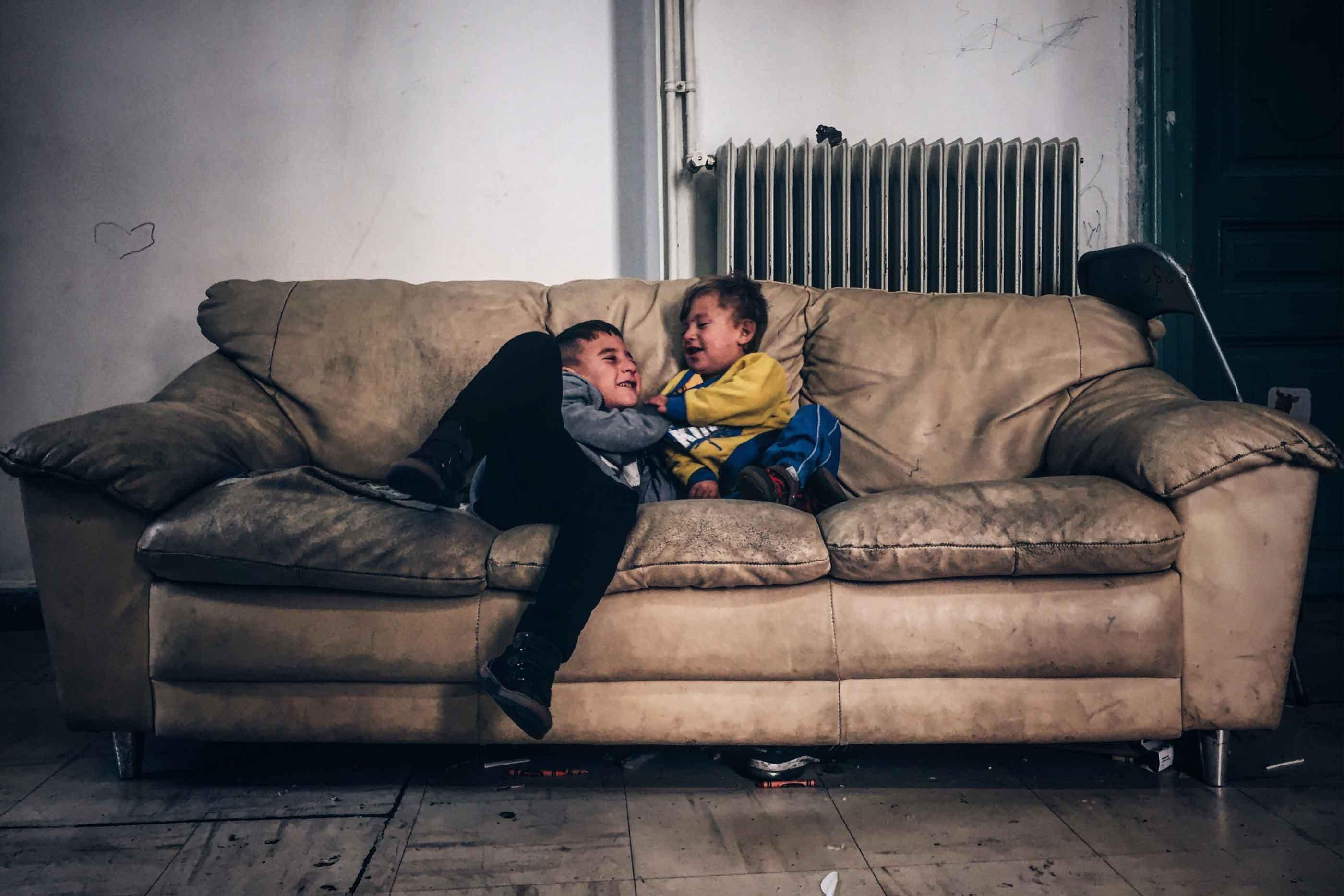 Irmãos brincam no sofá. CC by