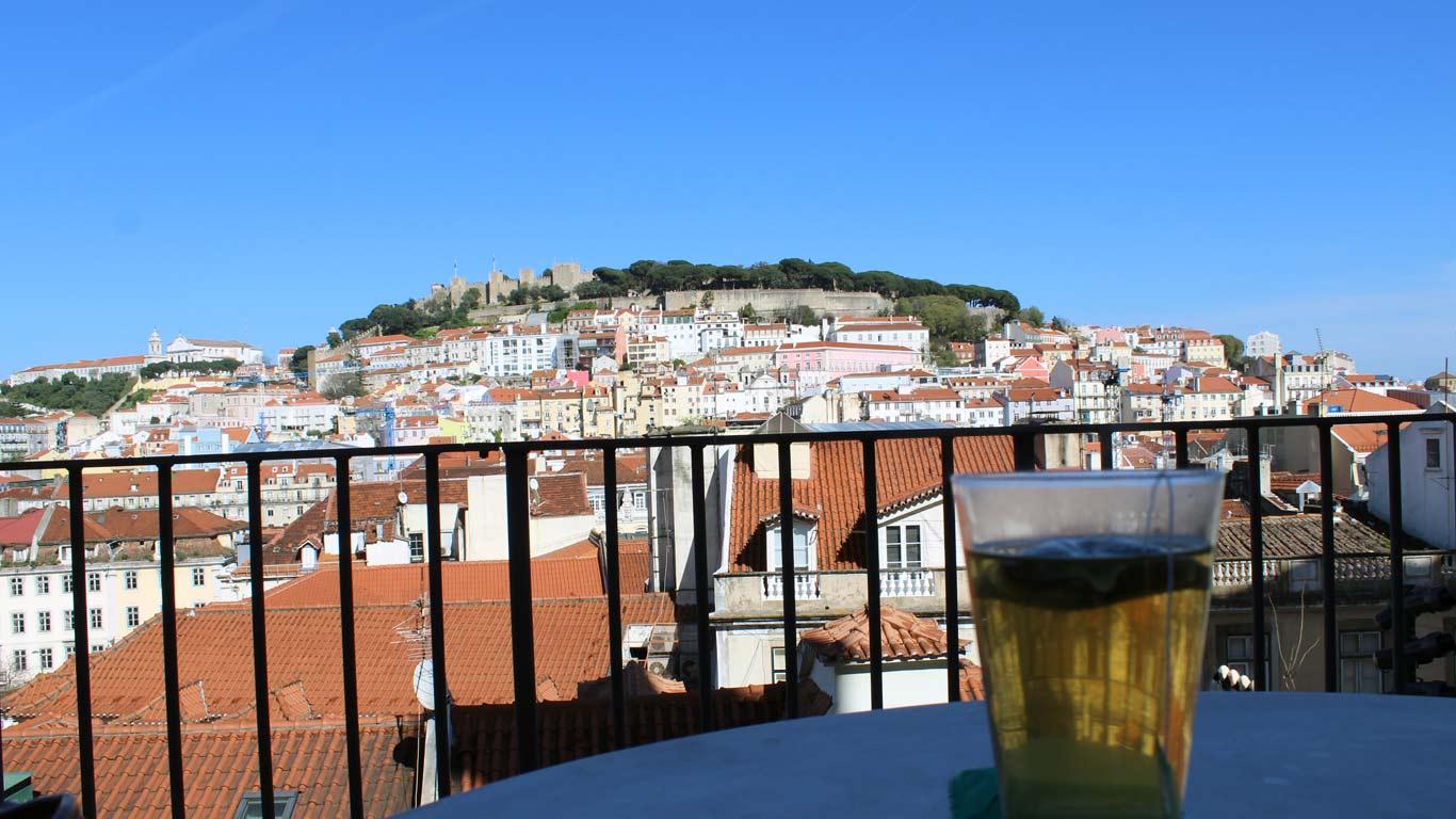 Imagem de promenor de uma das bebidas servidas no rooftop e no fundo imagem para zonha histórica de Lisboa