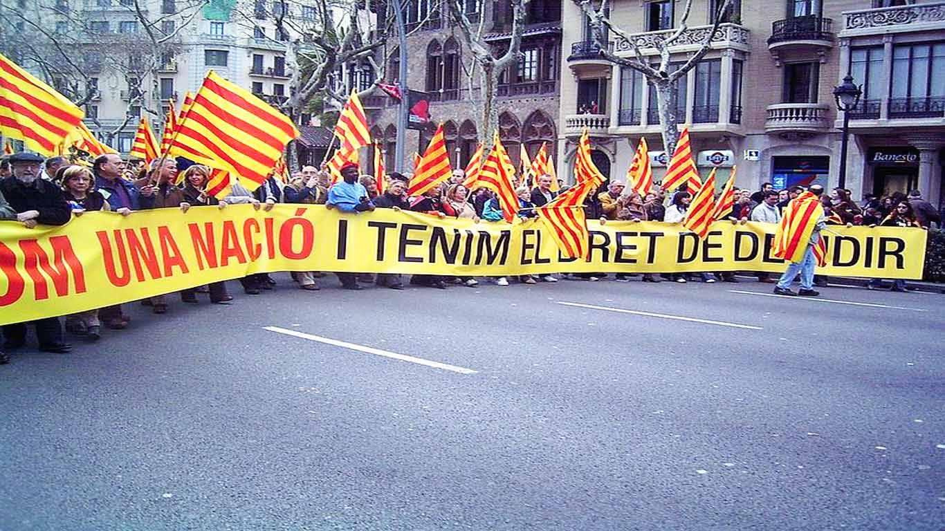 Manifestação em progresso, onde milhares de pessoas erguem bandeiras catalãs e uma tarja de revolta.