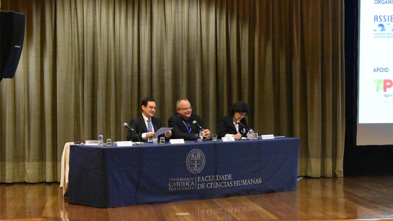 Diretor da Faculdade de Ciências Humanas, diretor do CECC e professora Isabel sentados na mesa principal do palco do auditório durante a sessão inaugural.