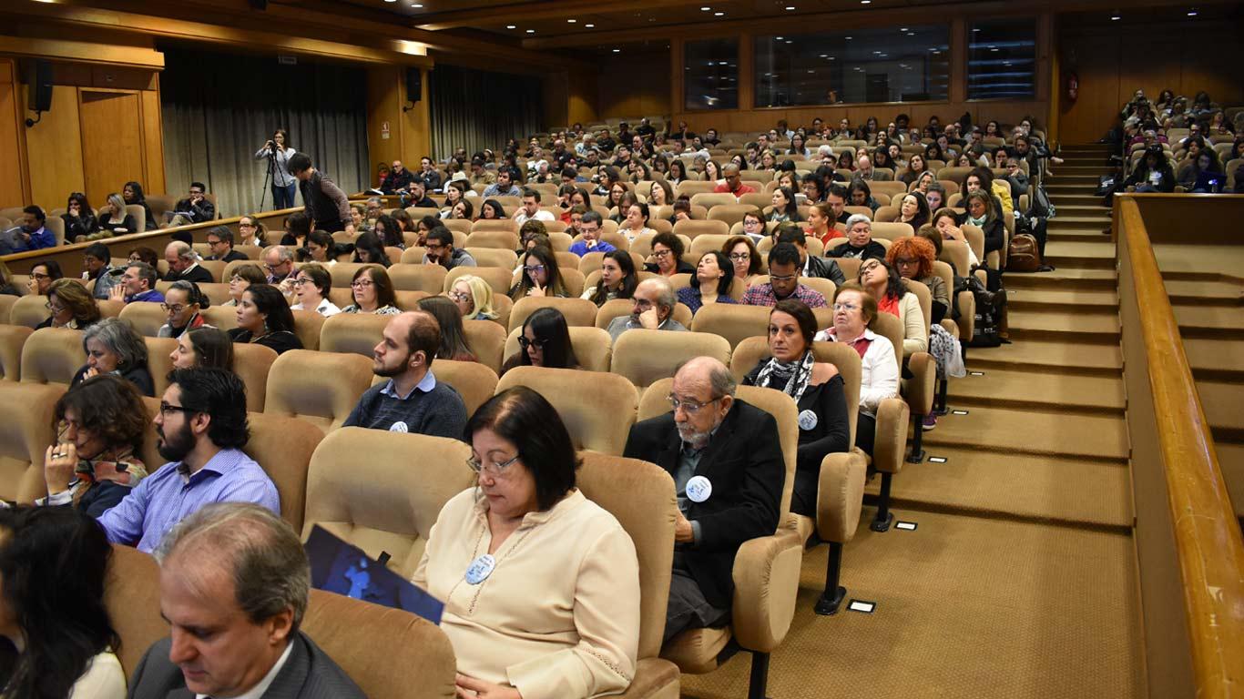 Foto tirada da frente do auditório, a pegar o público todo sentado e atento.