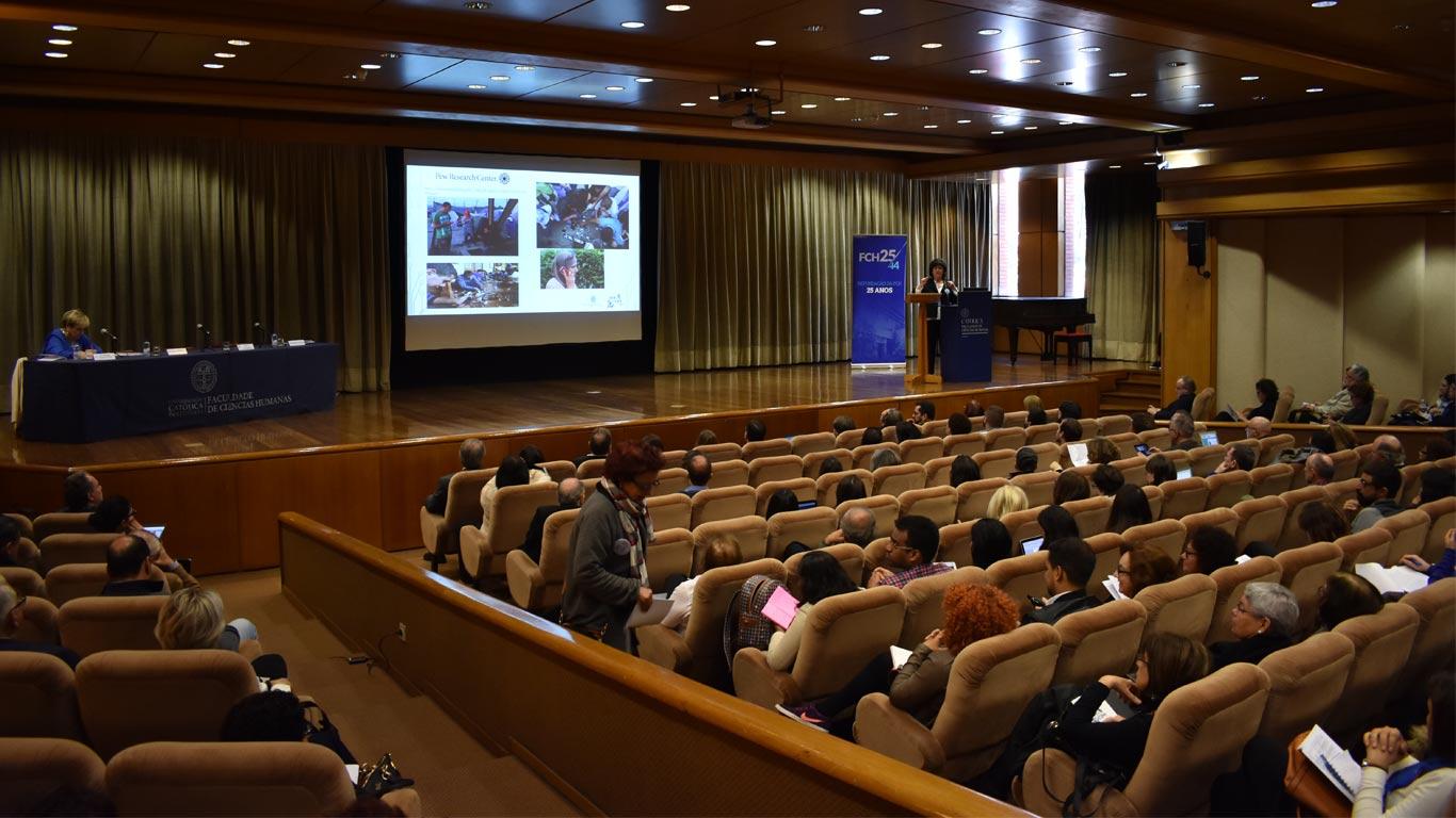 Foto tirada do meio do auditório, a pegar o público a frente e o palco, com a Prof Dra. Isabel a realizar o seu discurso.