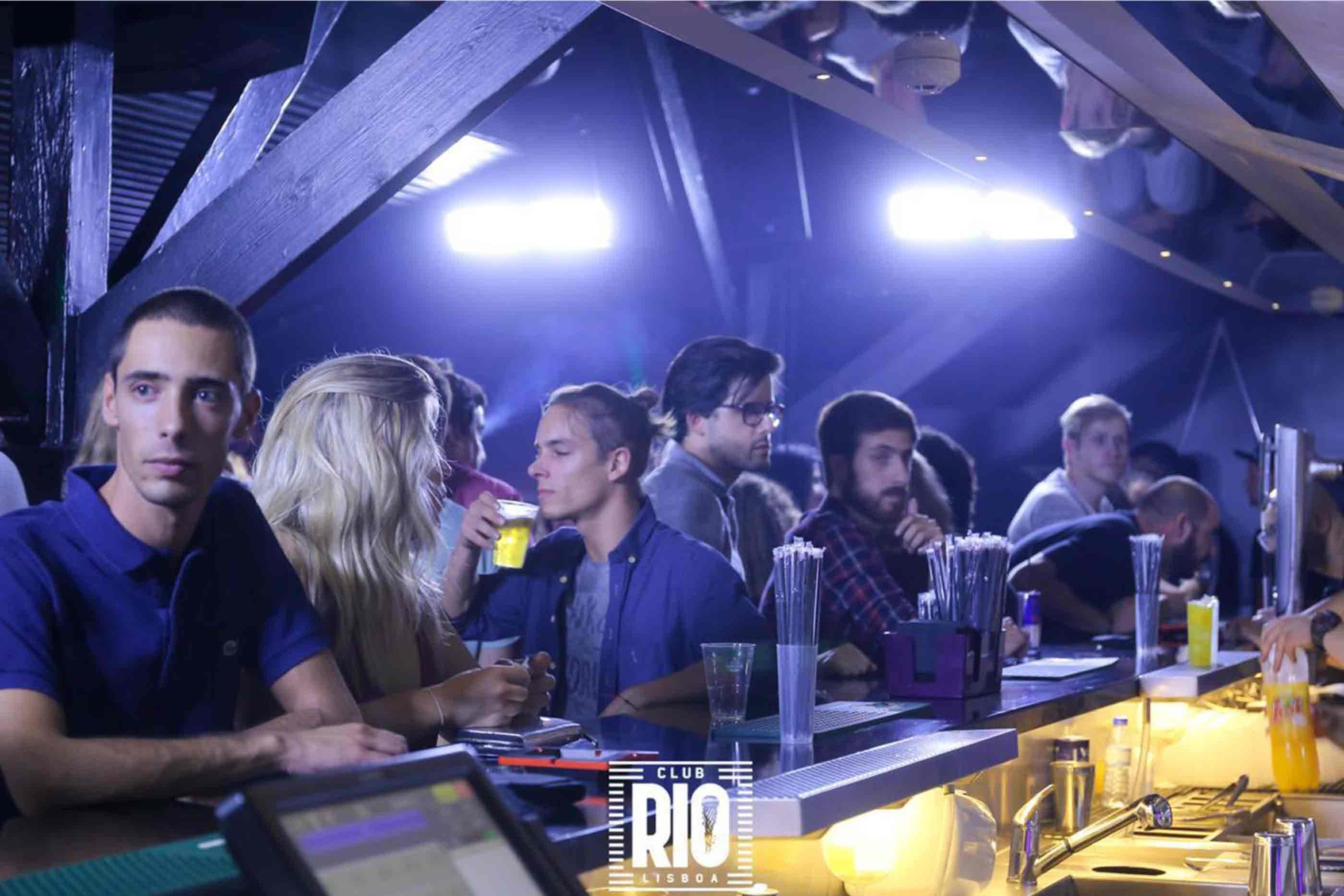 Pessoas no espaço junto ao bar acompanhados ao som da música.