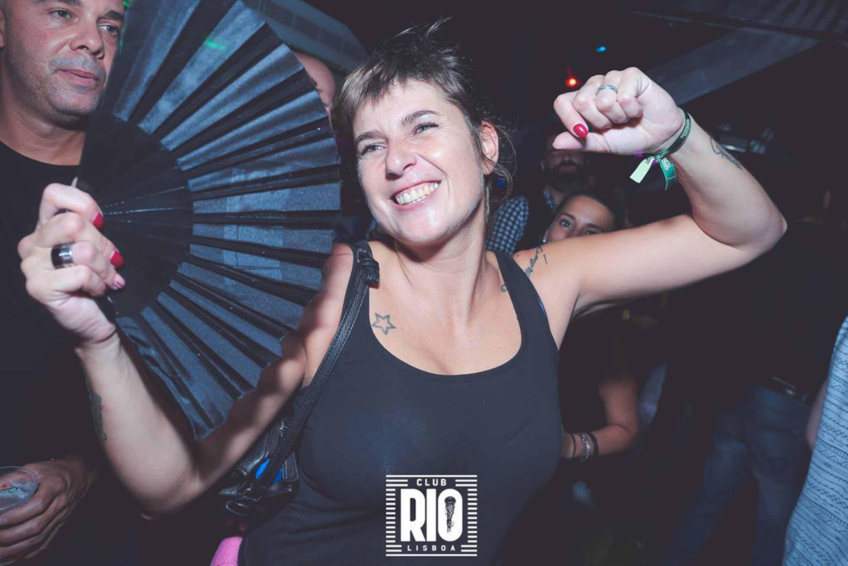 Rapariga feliz a dançar no Club Rio Lisboa com um leque na mão.
