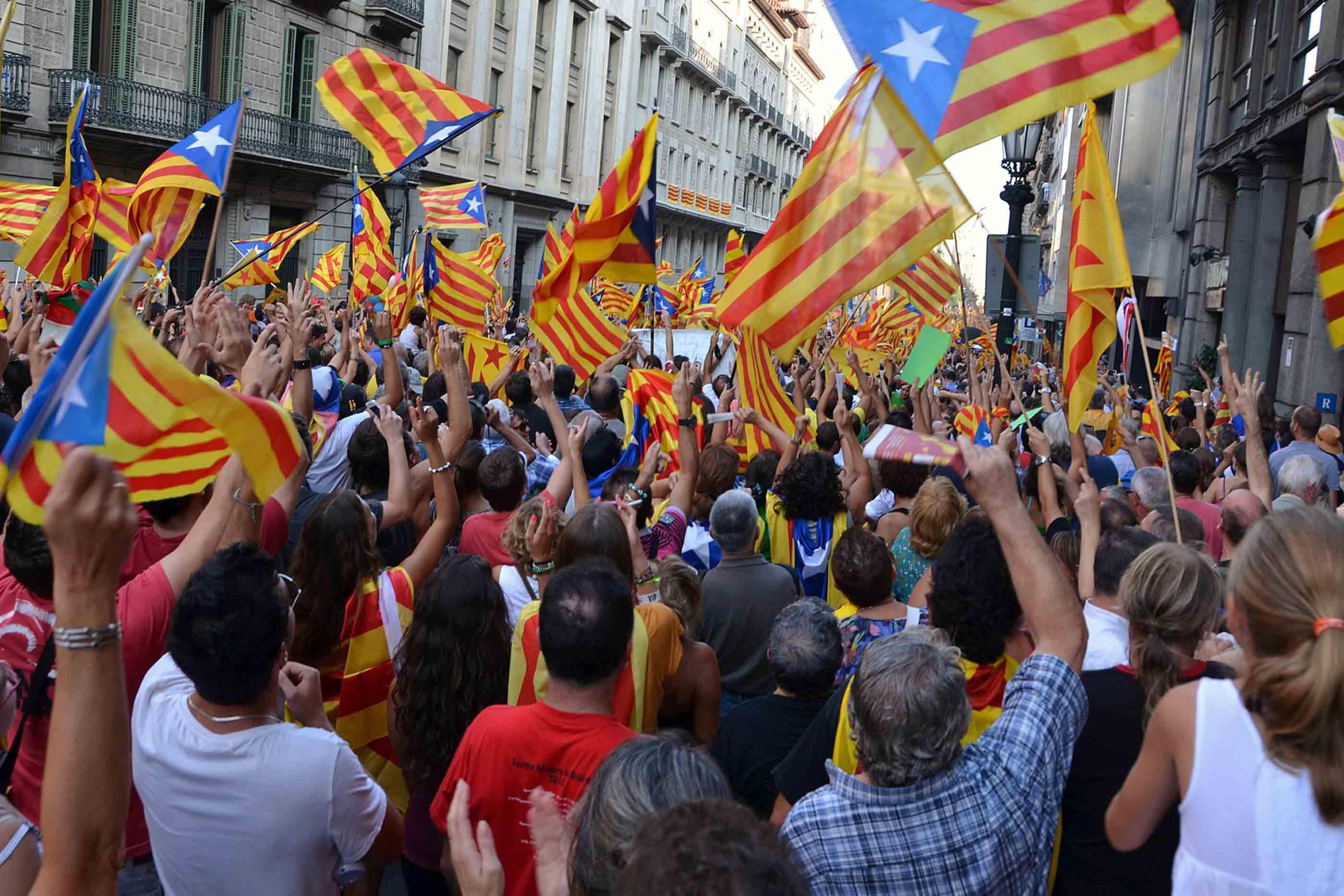 Catalães elevam as bandeiras na rua em protesto independentista.