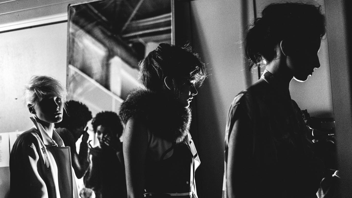 Fotografia a preto-e-banco do backstage da ModaLisboa. Observamos três modelos já prontas para entrar em passerele e uma quarta que está em frente a um espelho a dar os últimos retoques.