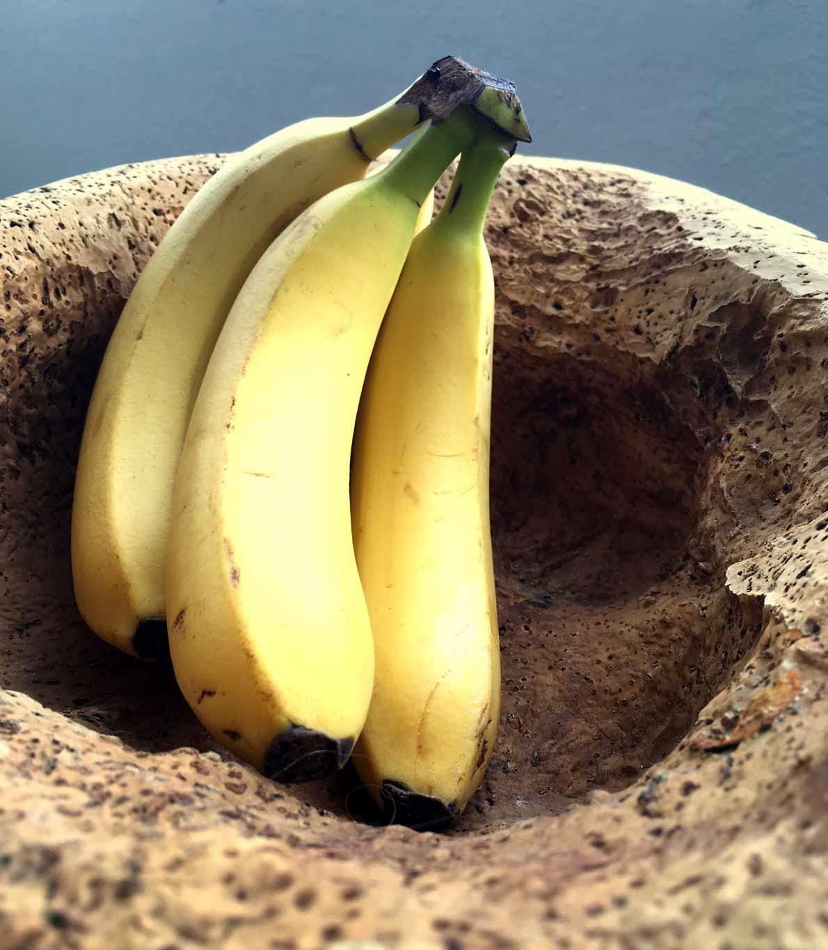 Um cacho de bananas deitadas num vaso feito de cortiça típico do Alentejo