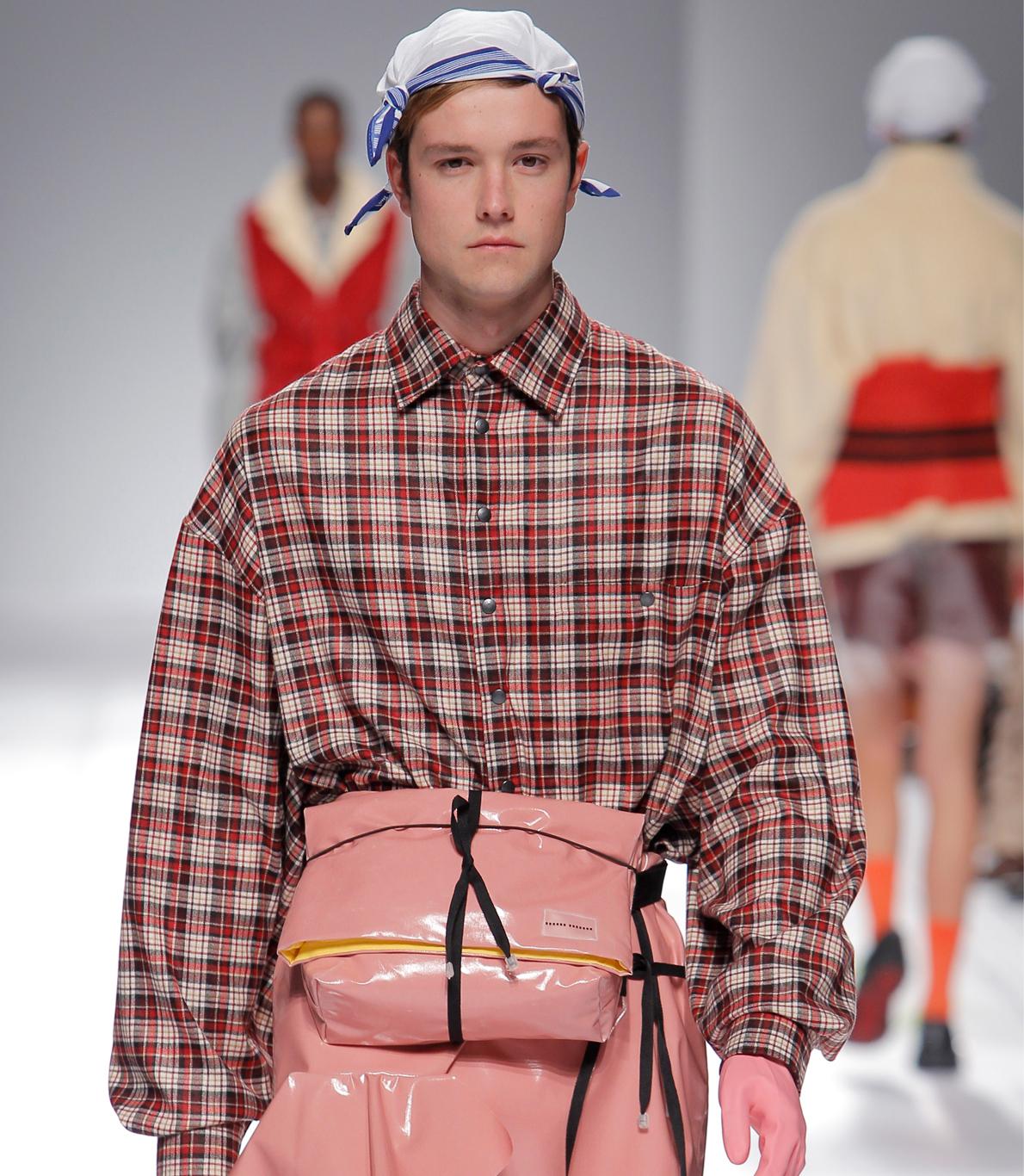 Modelo a desfilar com uma camisa de xadrez e uma bolsa à cintura em tons rosa. As calças laranjas e um lenço na cabelo completam o look.