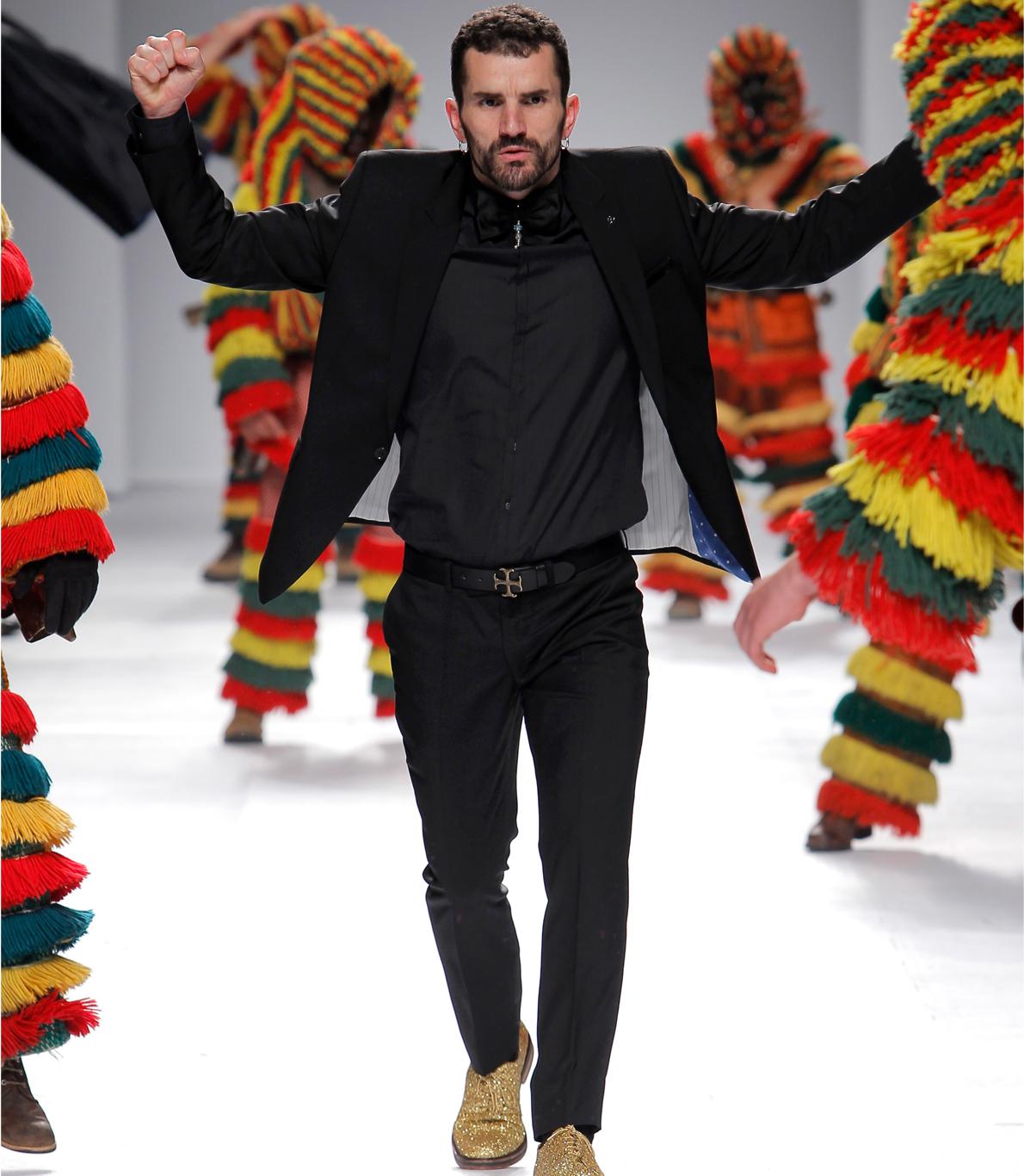 """Modelo a desfilar com um fato preto do design Nuno Gama. Ao fundo conseguimos observar os Caretos de Podence que """"invadiram"""" todo o desfile."""