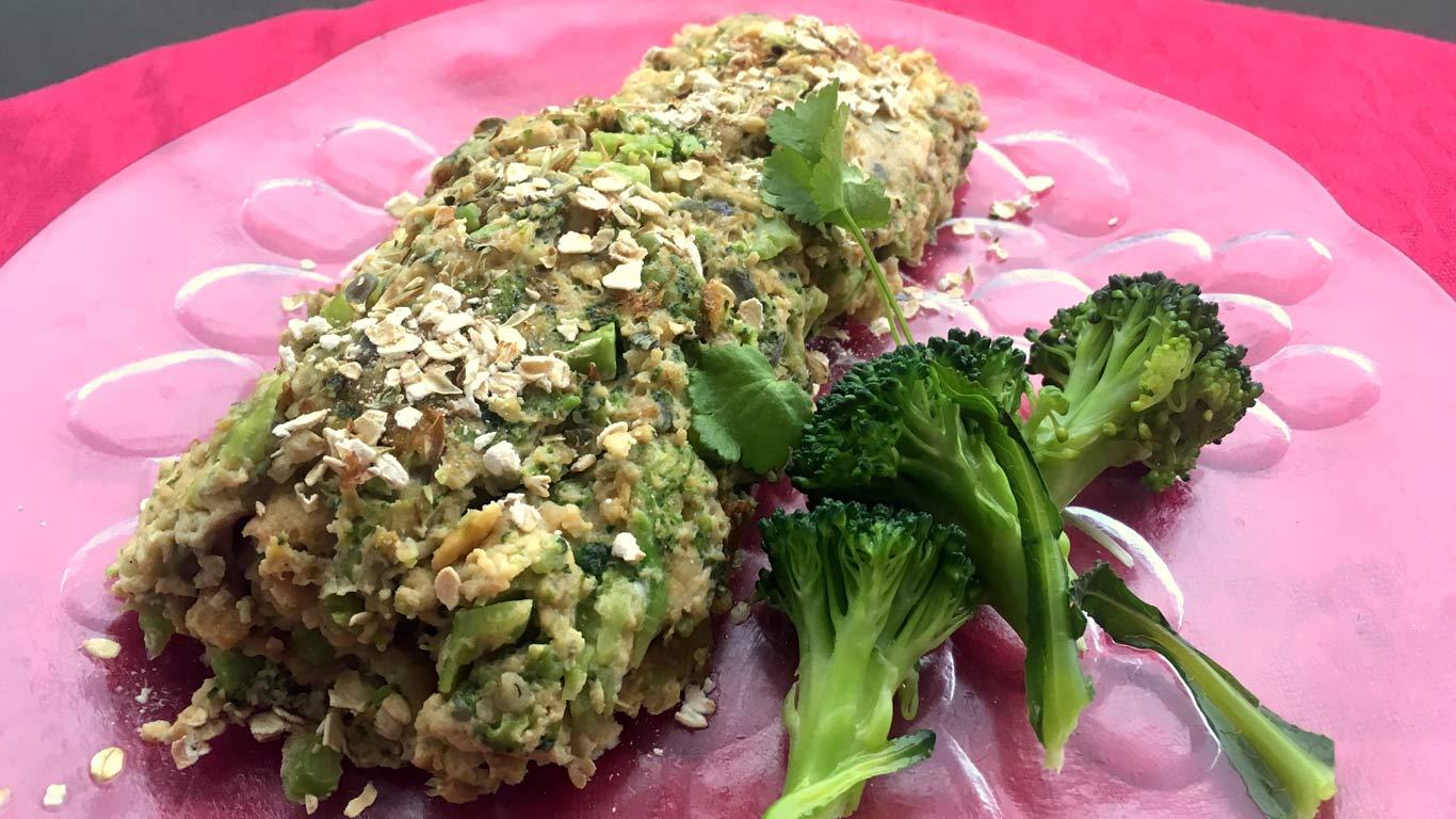 Uma omelete cozinhada com bróculos e aveia, decorada com sementes e acompanhada de bróculos.