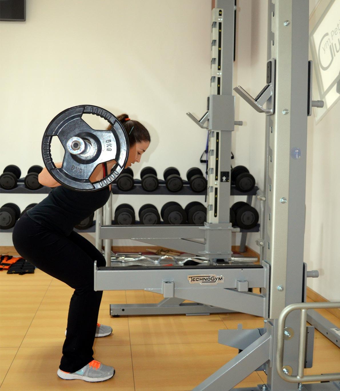 Rapariga que pega num peso e levanta-o com os braços, fletindo as pernas, para ganhar músculo.