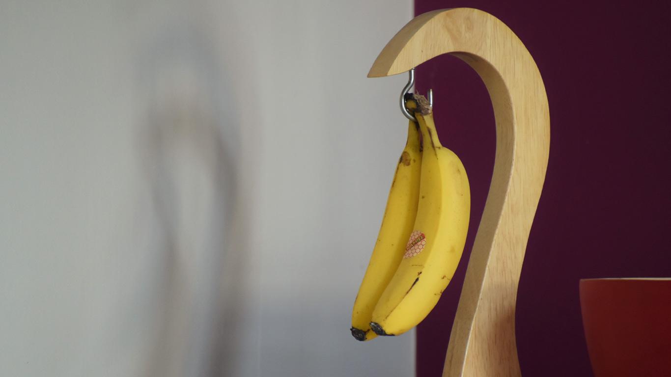 Imagem de um cacho de bananas amarelas penduradas num gancho de madeira.