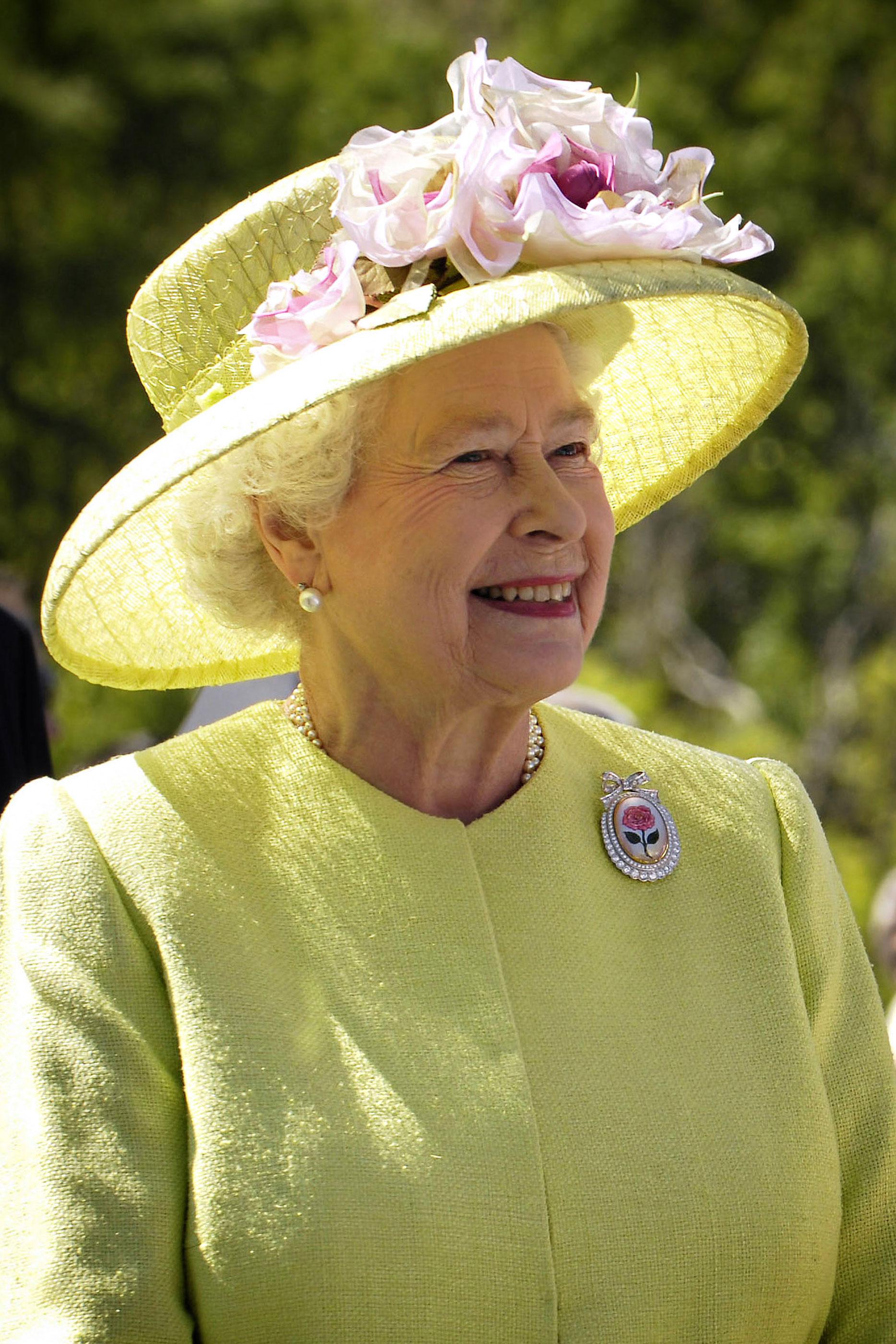 Rainha Isabel II com um vestido verde e um chapéu da mesma cor, com um pormenor dumas rosas na pala.