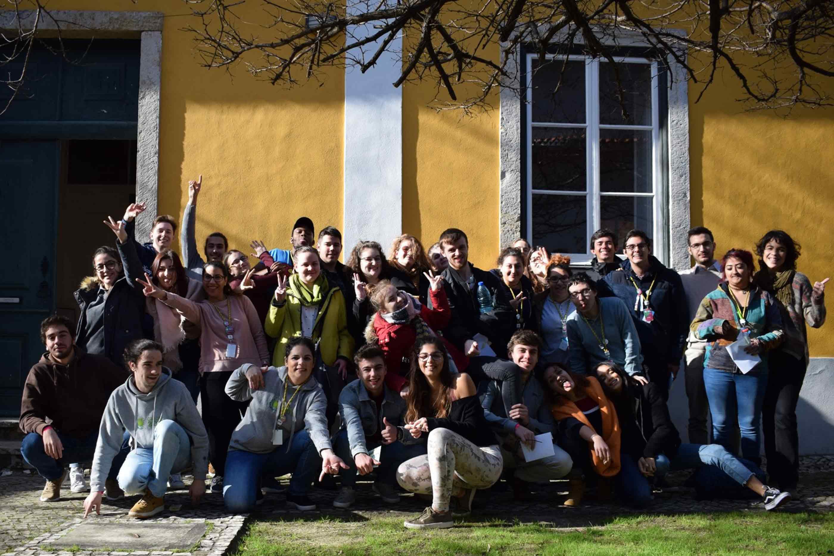 Fotografia do grupo de jovens no exterior de um edificio amarelo.