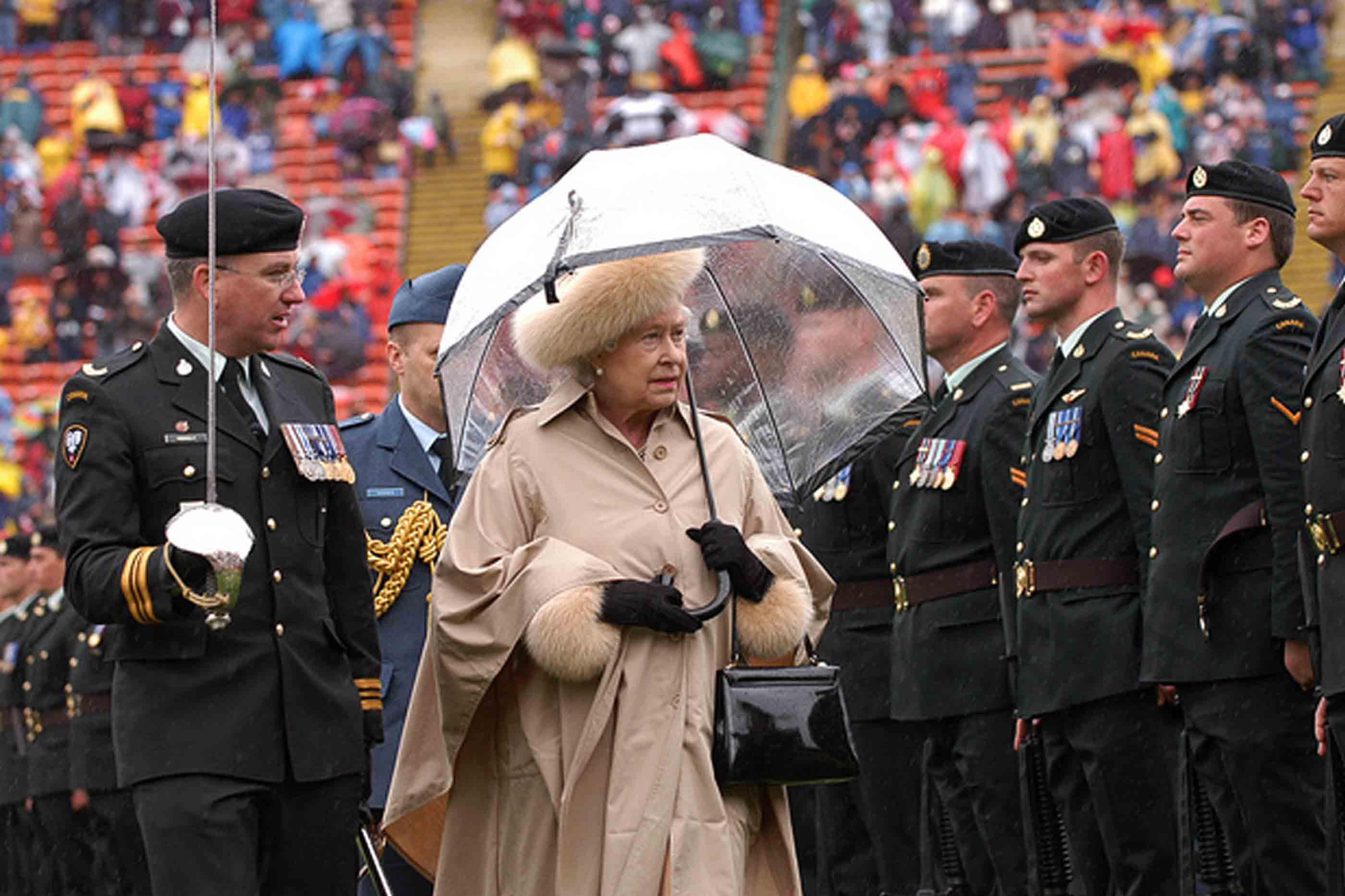 Rainha Isabel num dia chuvoso, de chapéu de chuva aberto, a cumprimentar os militares em formatura.