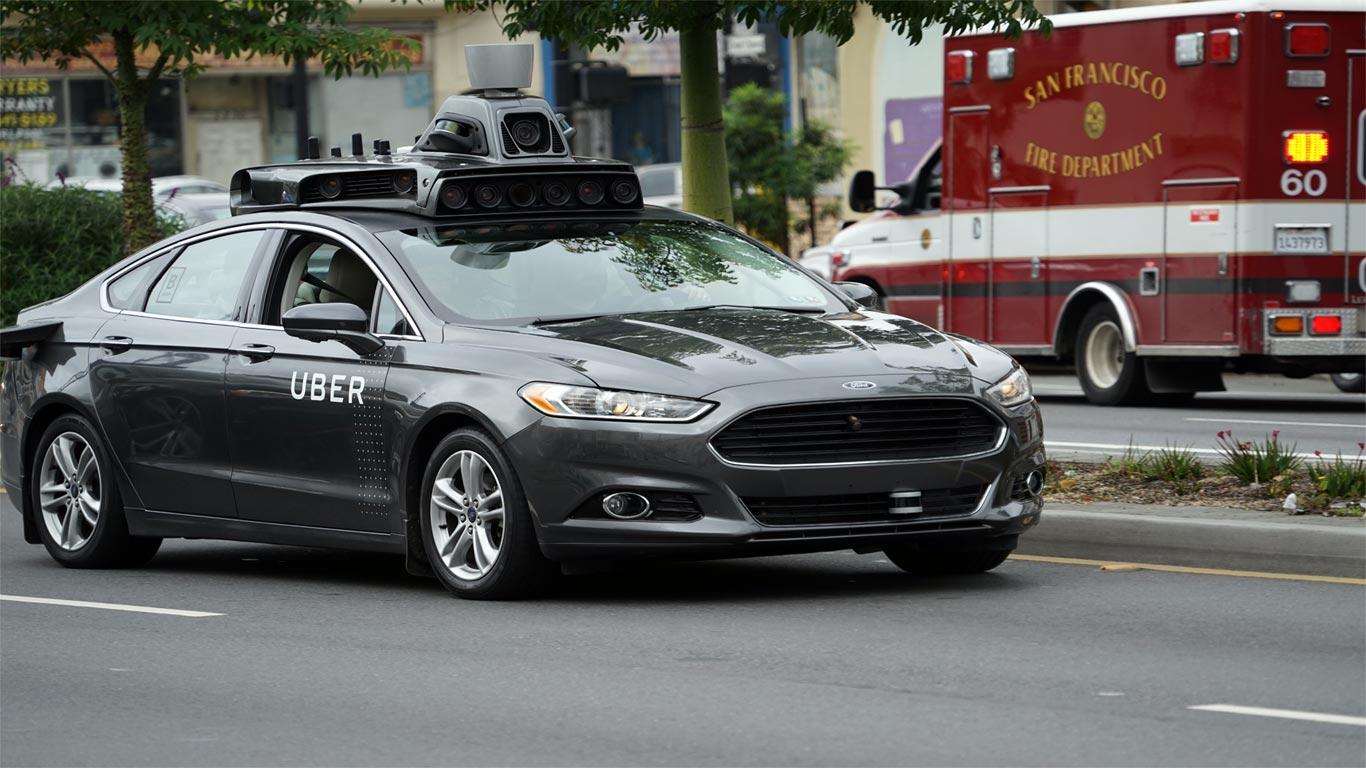 Carro privado da empresa Uber equipado com megafone e sistema de luzes no tejadilho, a circular em uma via pública em São Francisco, Califórnia.