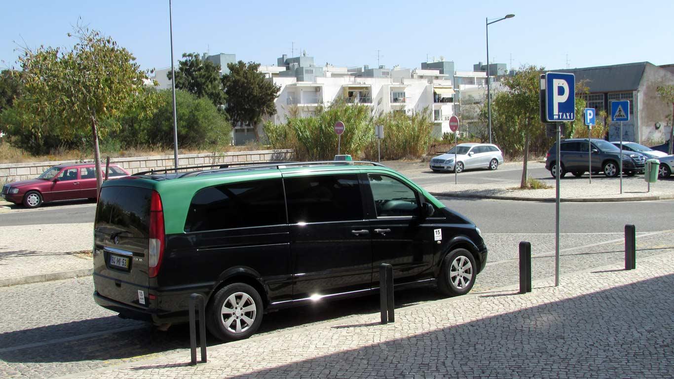 Motorista de táxi em carrinha estacionado em praça de táxi.