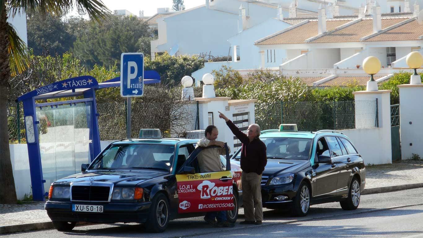 Dois taxistas a conversar estacionados em praça para taxis no Algarve.