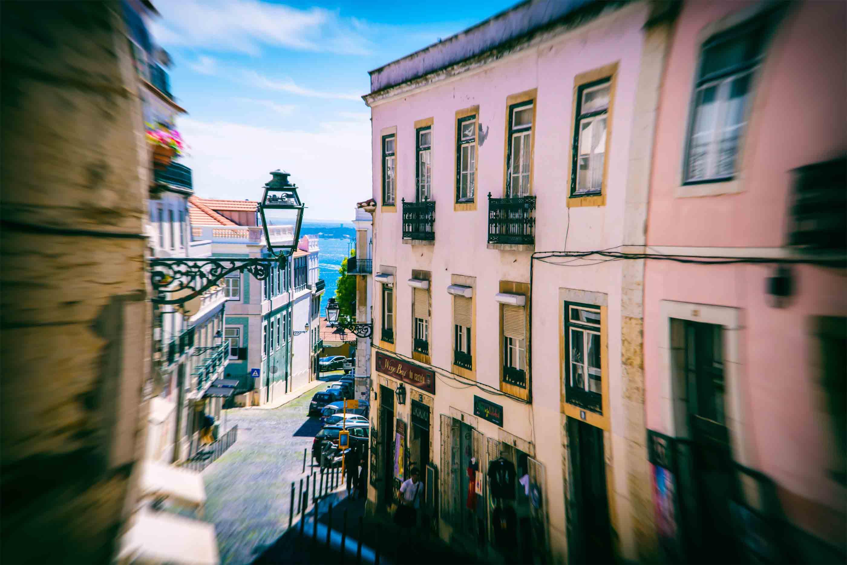 Rua em Lisboa, entre prédios, que desce em direção ao rio.