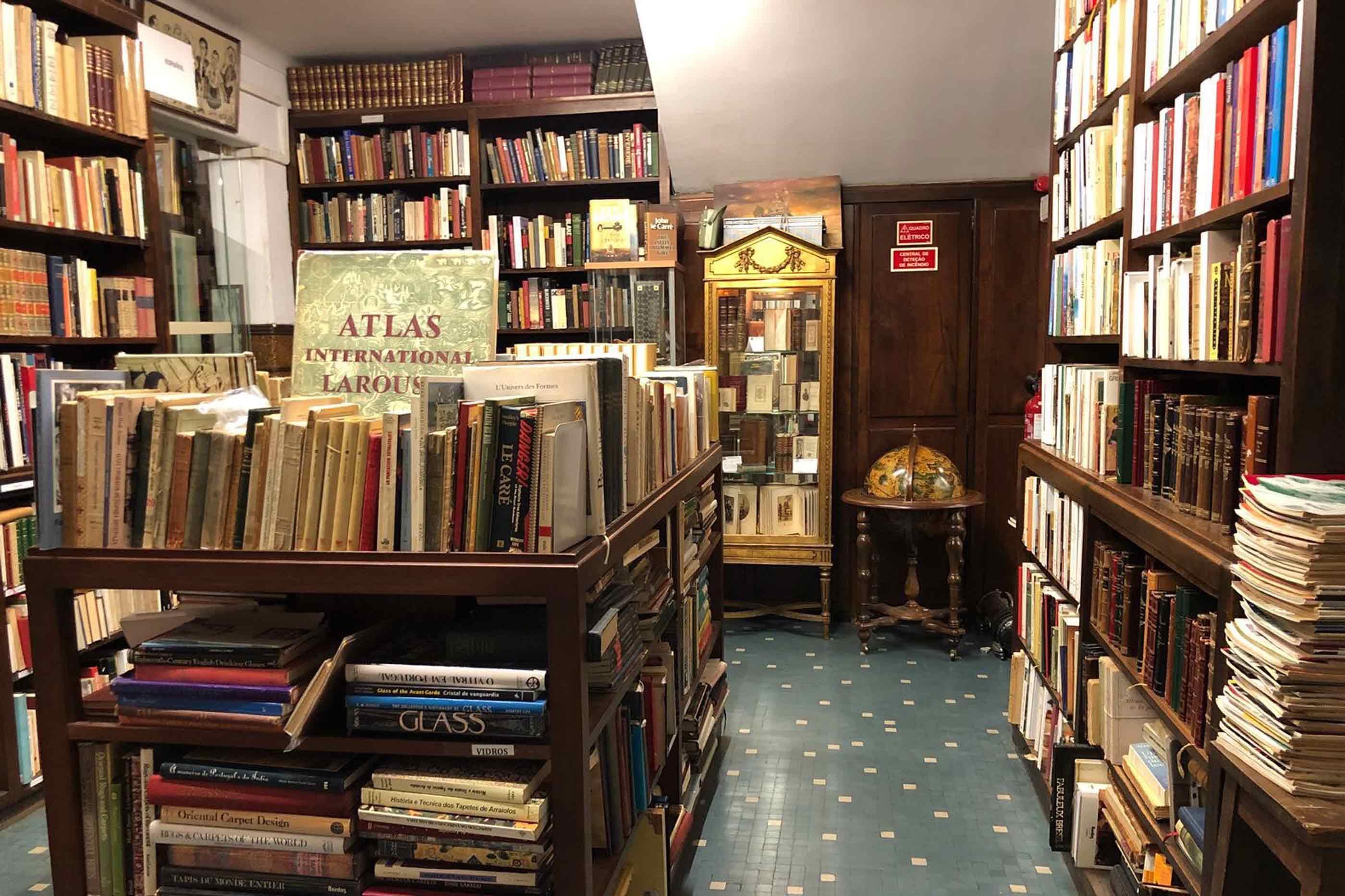 Uma mesa repleta de livros encontra-se do nosso lado esquerdo. Em frente, encontra-se uma vitrine dourada, com vários livros abertos e devidamente identificados. Ao seu lado, está um globo num suporte de madeira.