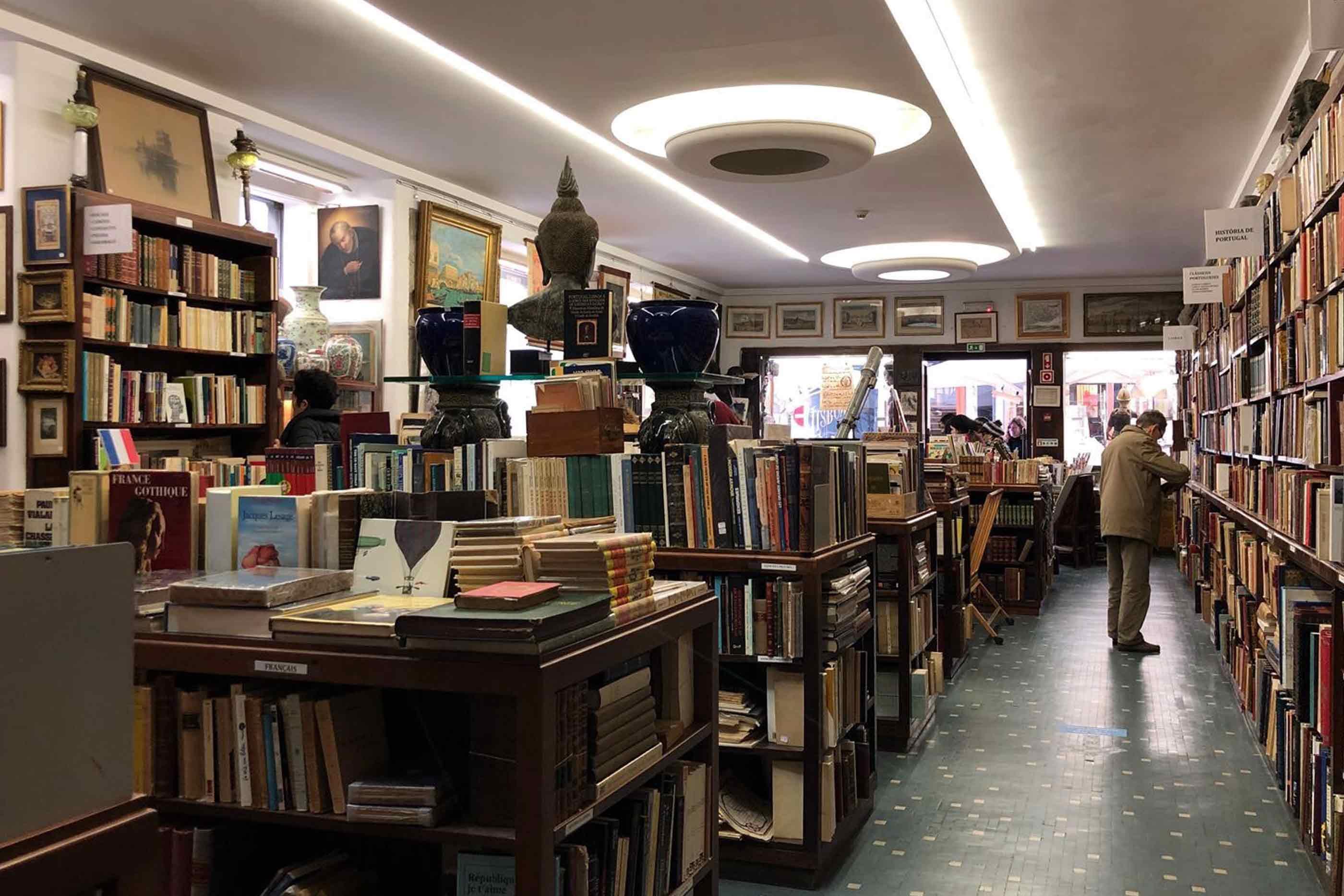 Do nosso lado direito, estão várias estantes repletas de livros e outros objetos curiosos - um busto de um Buda, uma jarra grande e azul ao centro da sala e nos espaços vazios das paredes são ocupados por quadros.