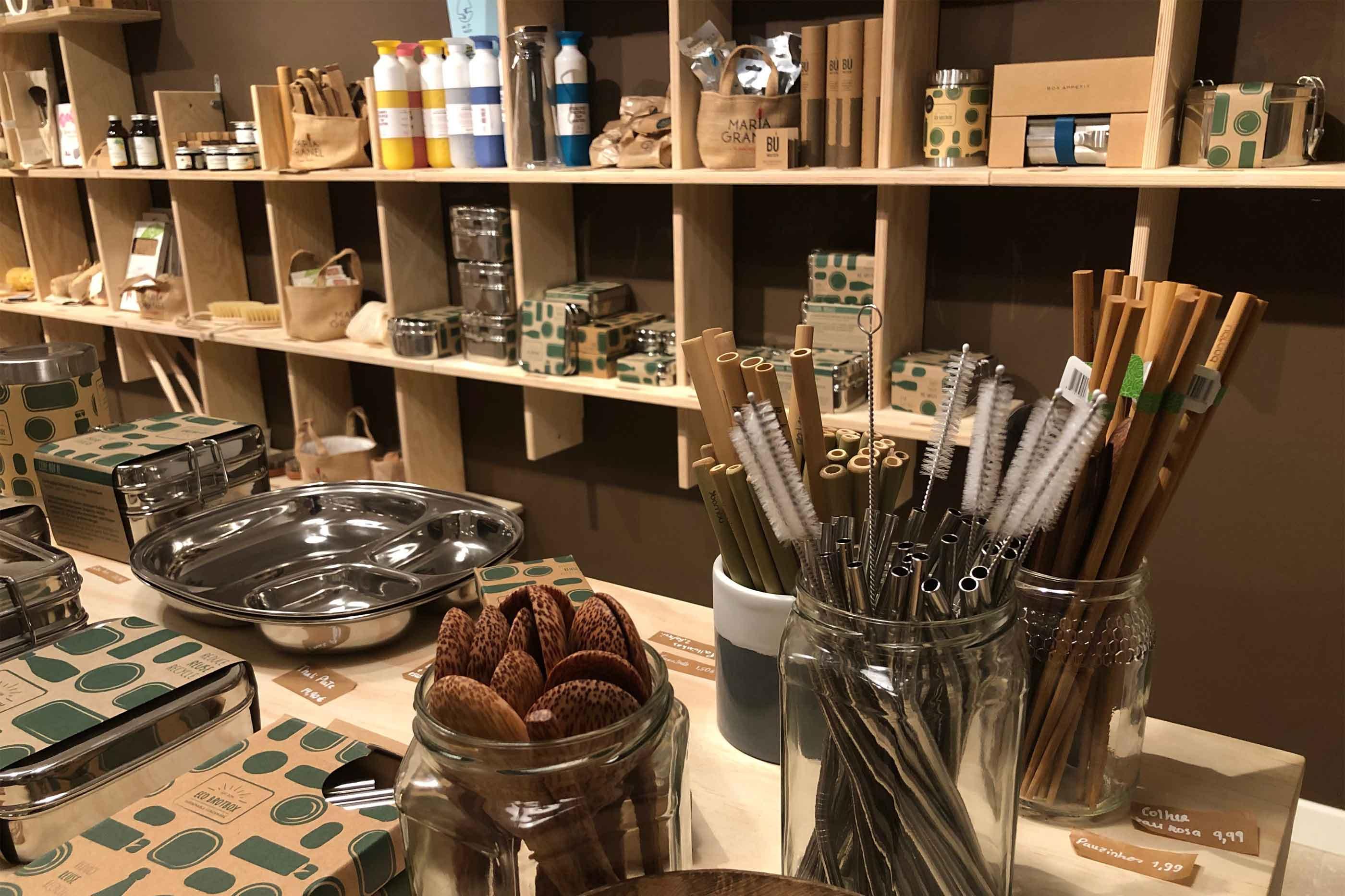 No andar inferior da loja podemos encontrar vários objetos zero waste. Em destaque, nesta fotografia, encontramos as palhinhas de bambu e de aço inoxidável, ao lado de colheres e pauzinhos de madeira.
