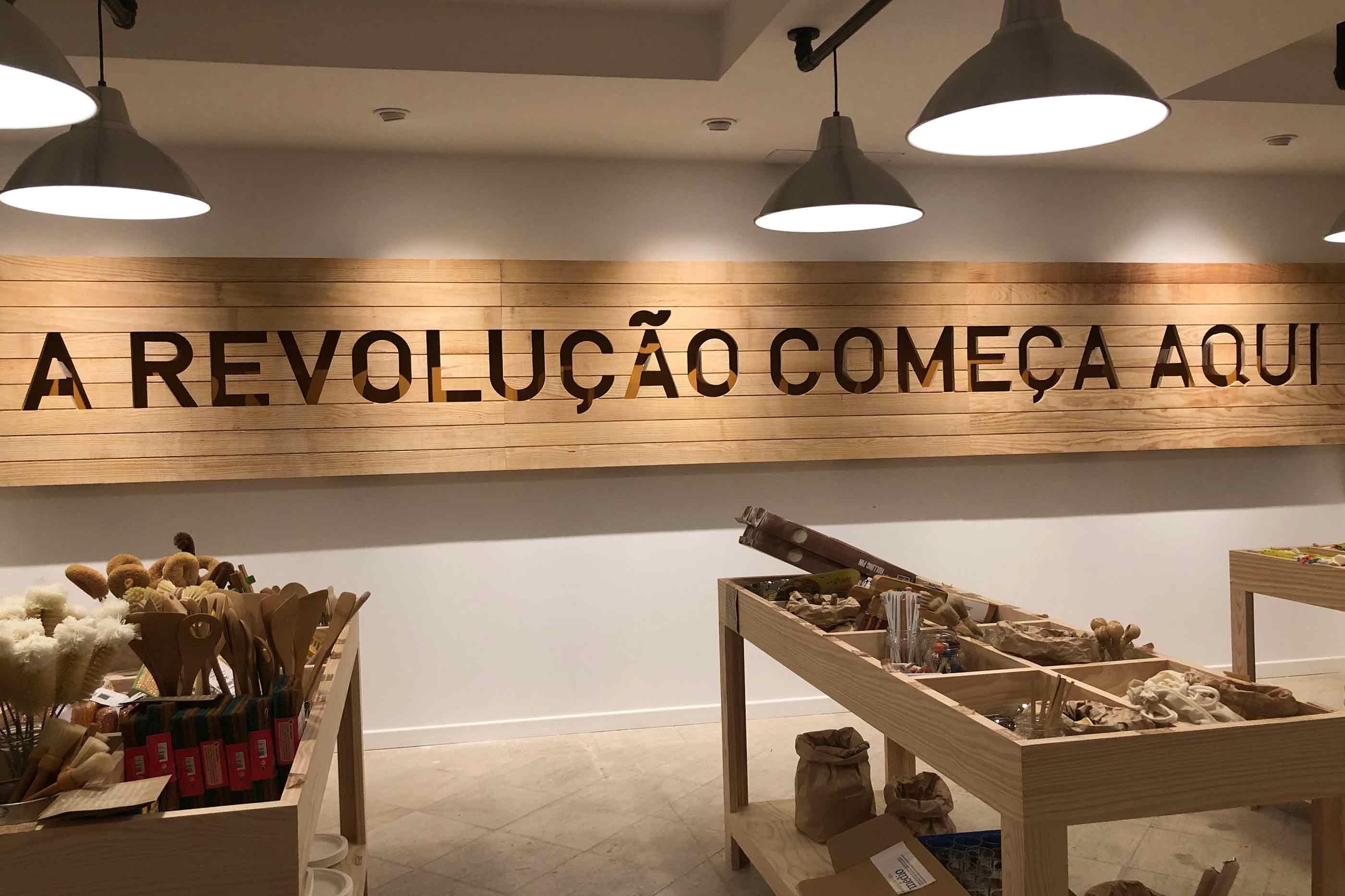 """No andar inferior da loja de Campo de Ourique podemos observar várias estantes com produtos zero waste, vemos um espaço que percebemos ser aquele que é dedicado aos workshops e ao fundo, a ocupar toda a parede, encontramos uma placa em madeira que diz """"A REVOLUÇÃO COMEÇA AQUI""""."""
