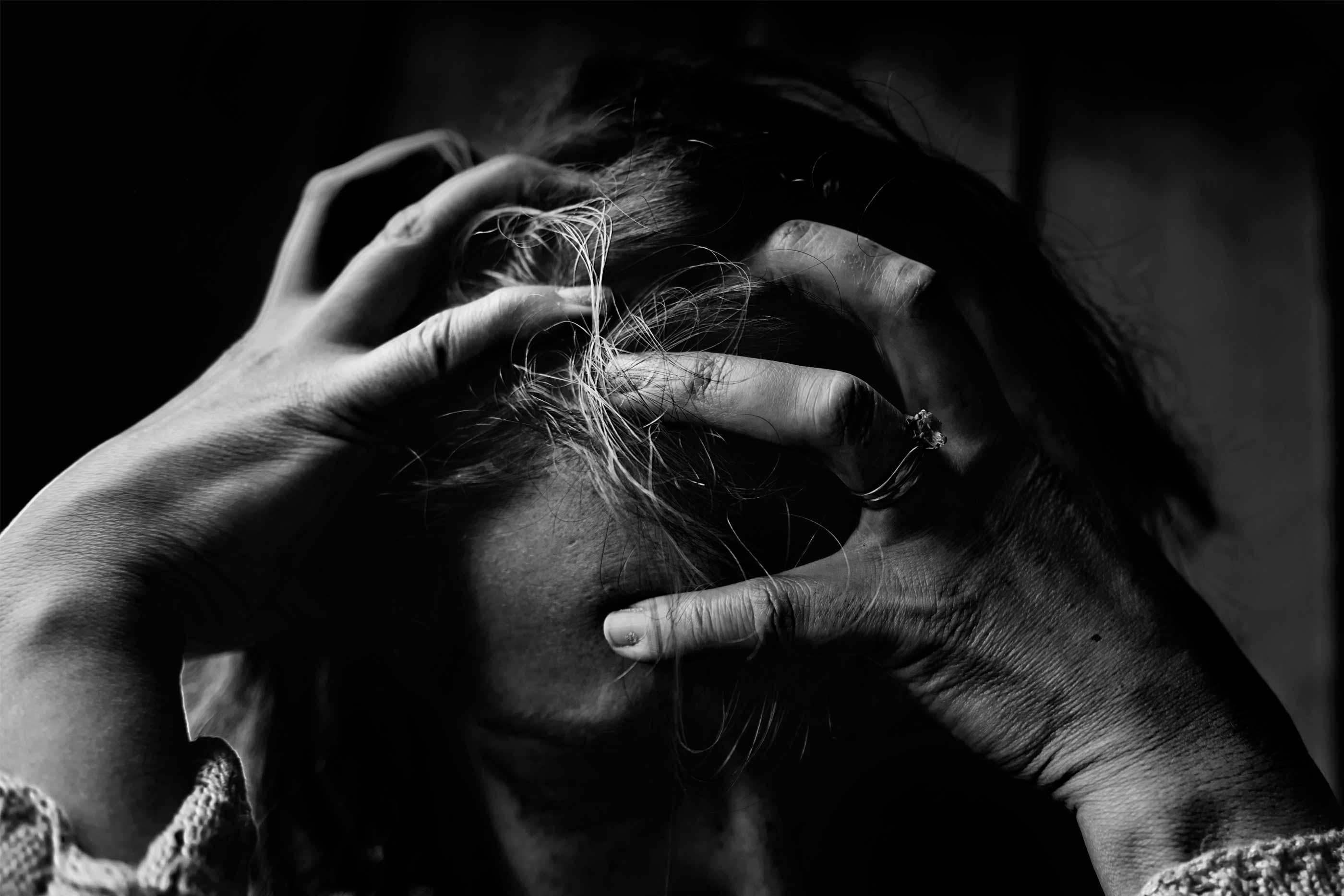 Imagem a preto e branco mostra uma mulher com as mãos na cabeça e a ter um esgotamento nervoso. Está em lágrimas e quase a arrancar os cabelos.