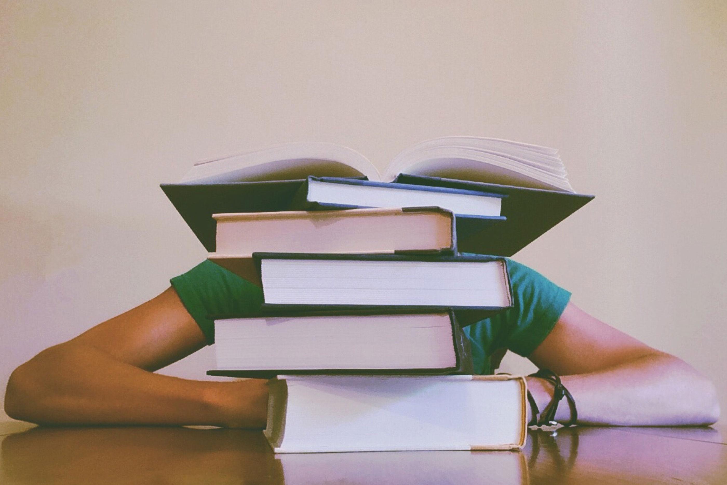 Vários livros empilhados numa mesa, representando o excesso de trabalho que o aluno terá de fazer. A quantidade de livros é tanta que não dá para ver a cara da pessoa. A pessoa está debruçada sobre a mesa.