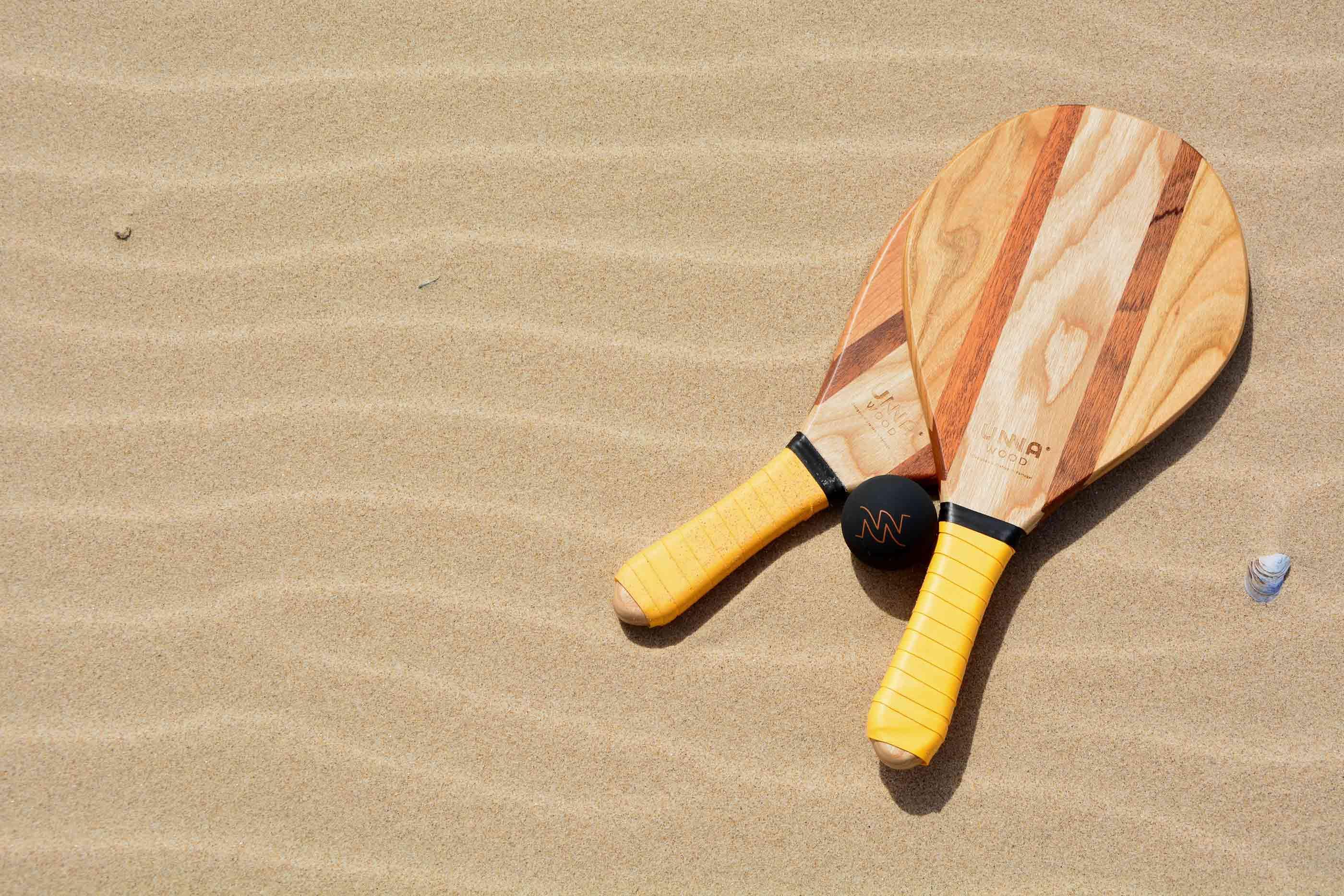 Duas raquetes de praia e uma bola preta pousadas no areal de um praia