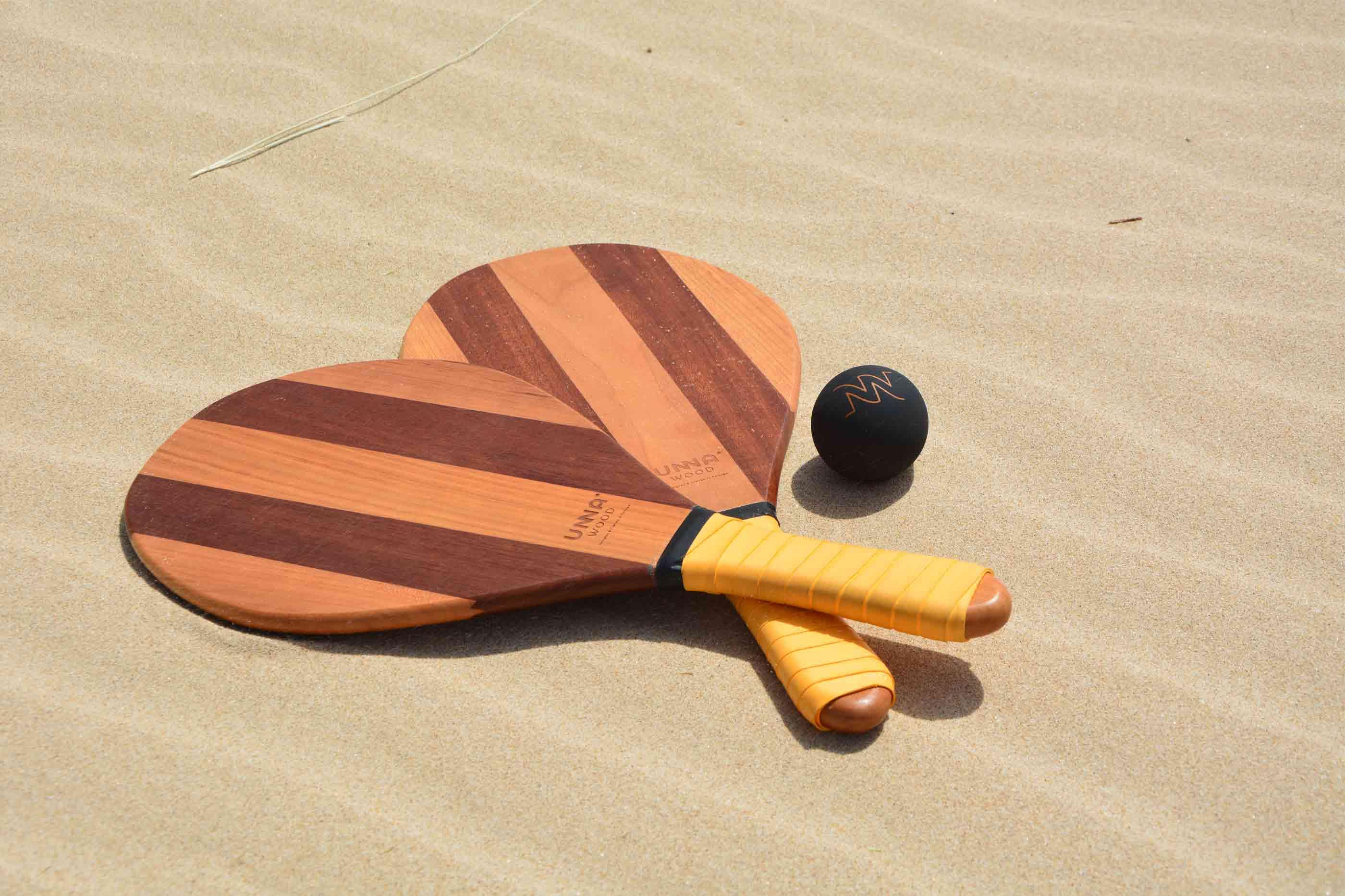 Duas raquetes de praia e uma bola preta na areia