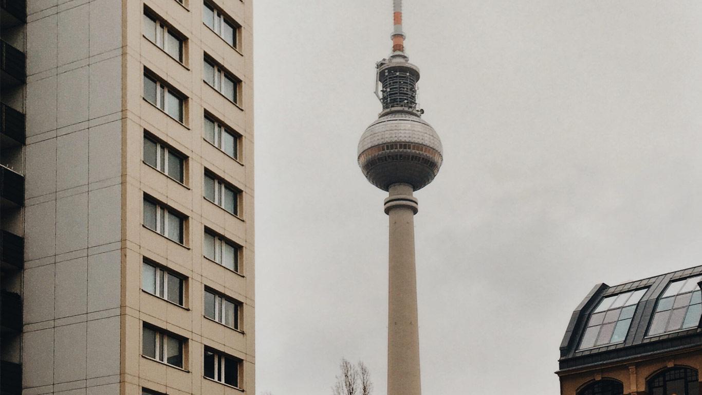 Vista de um ponto da Alexanderplatz em Berlim com foco para a torre Fernsehturm num dia nublado.