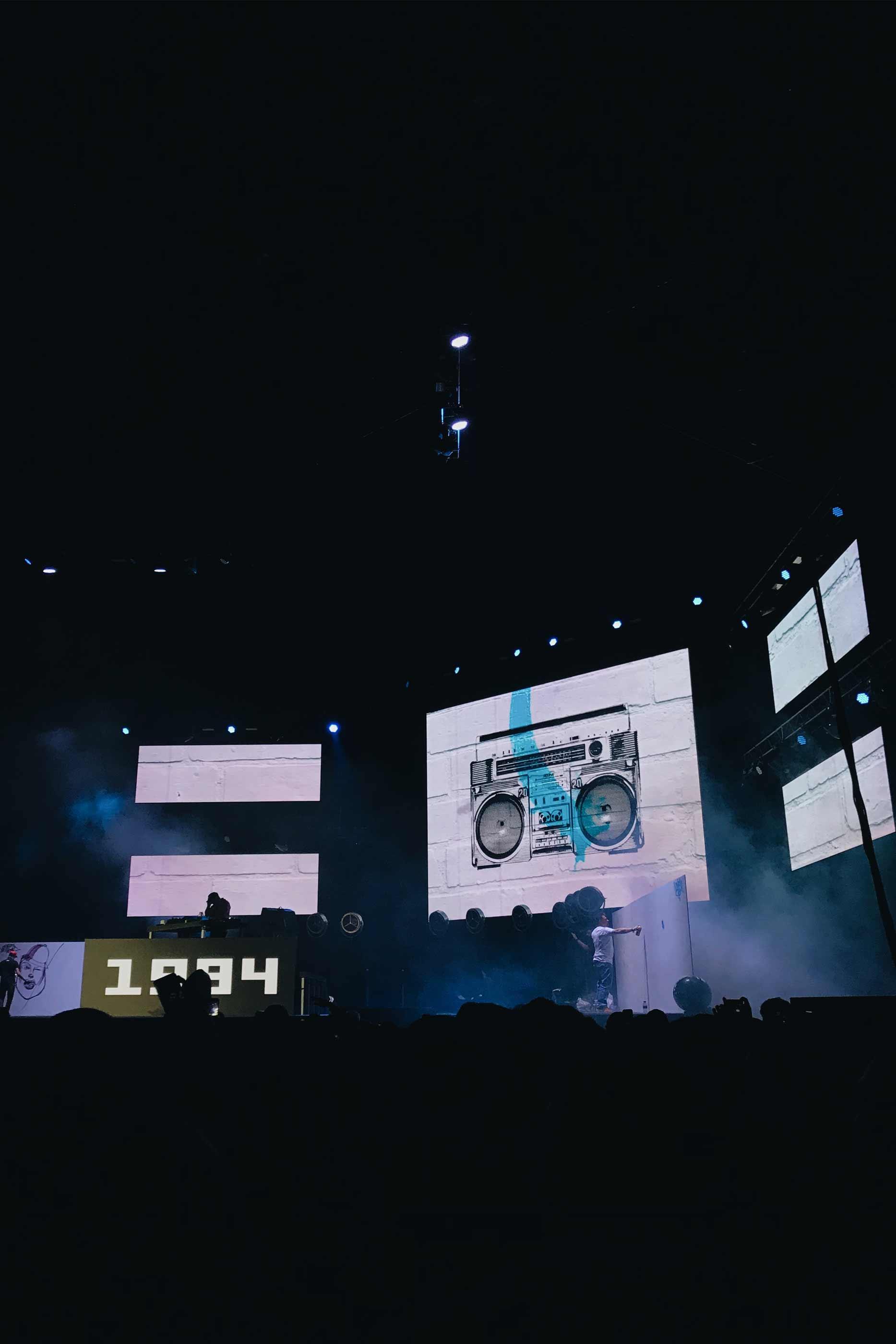 """Imagem parcial do palco, ecrãs luminosos com projeções de rádio e do ano de """"1994"""""""