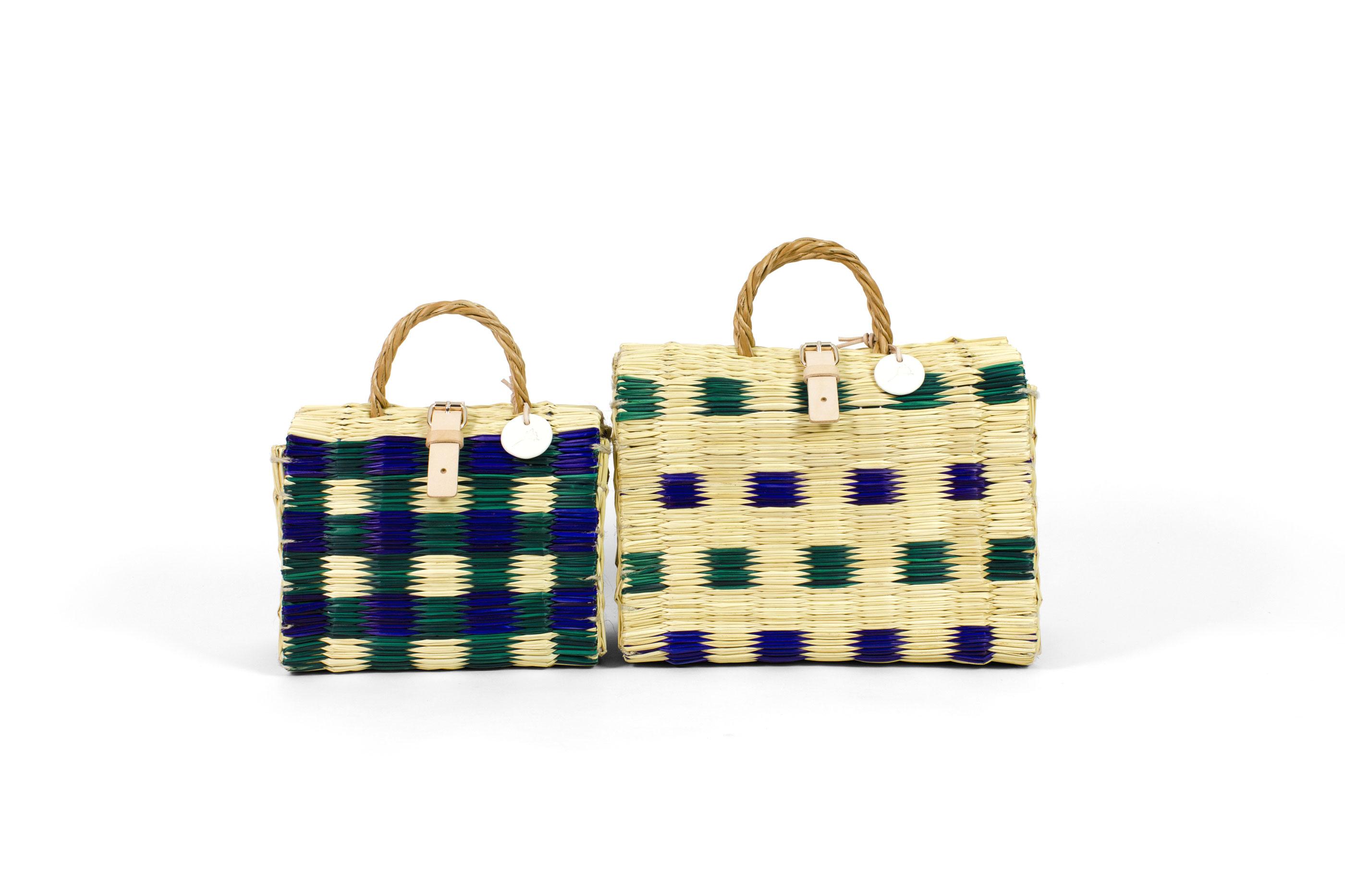 """Malas """"Celeste"""" e """"Olinda"""", tendo um pano de fundo branco, dois dos artigos da marca TOINO ABEL, feitos de junco e vime, com um padrão tingido a azul e verde."""