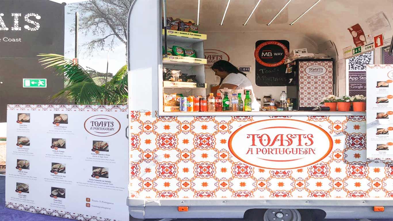 """Fotografia da zona de restauração do Estoril Open – Pátio do Estoril -, apresentando uma das roulotes, """"Toasts à Portuguesa"""", com o menu disponível do lado esquerdo."""