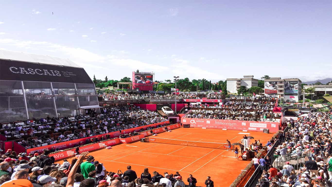 Fotografia do court principal do Estoril Open – Estádio Millennium -, durante a tarde onde se realizou a partida final do Estoril Open 2019. Na fotografia os jogadores estão a preparar-se para dar início à partida.