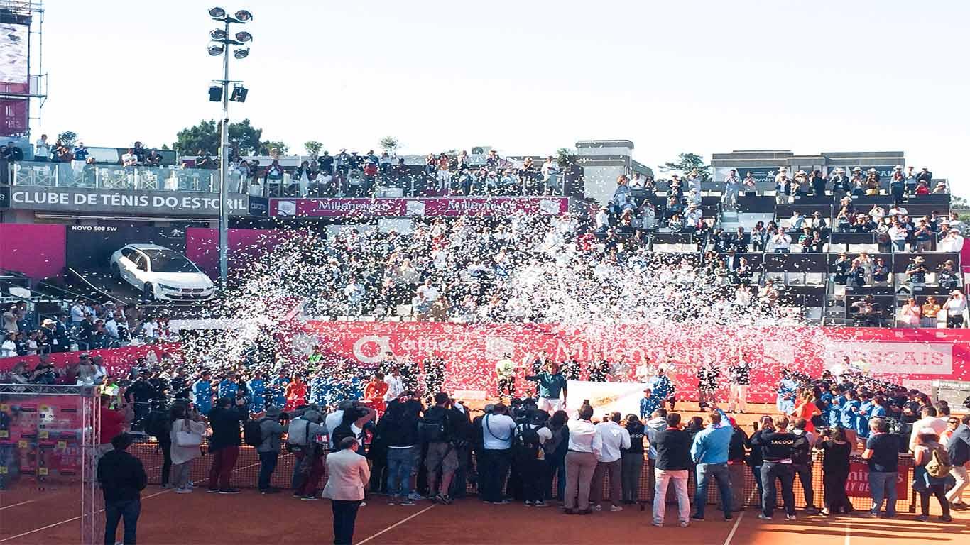 Fotografia da entrega do prémio ao vencedor do Millennium Estoril Open, Stefanos Tsitsipas, e todo o festejo com confetes e champanhe. À sua volta, todos os responsáveis, voluntários do torneio e vários jornalistas a tirarem fotografias do acontecimento.