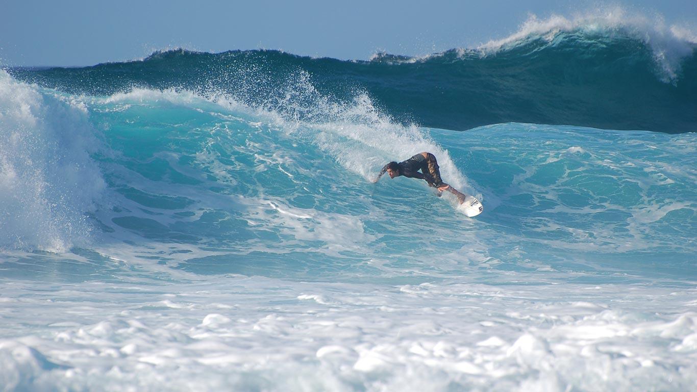 Surfista a surfar uma onda grande numa das praias mais conhechidas munidalmente