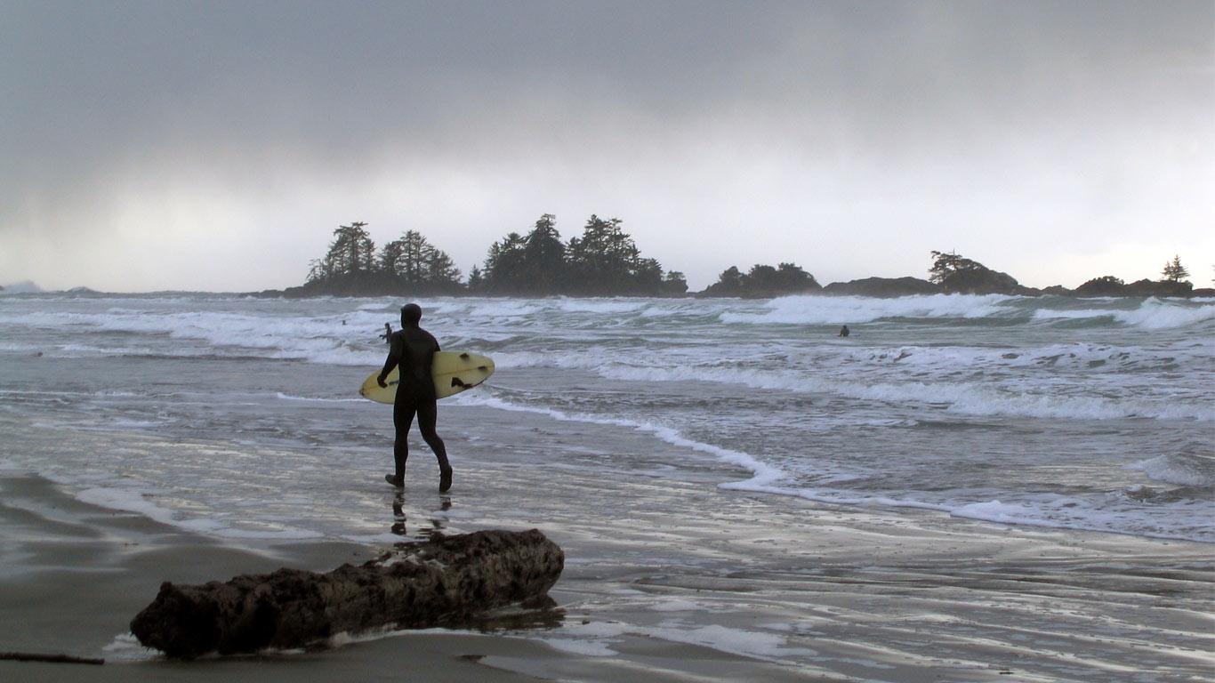 Surfista caminando ao longo do areal com a sua prancha na mão