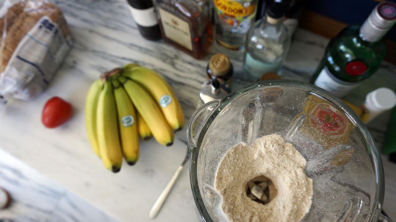 Fotografia tirada de cima a alguns componentes necessários para as receitas e no backround algumas garrafas