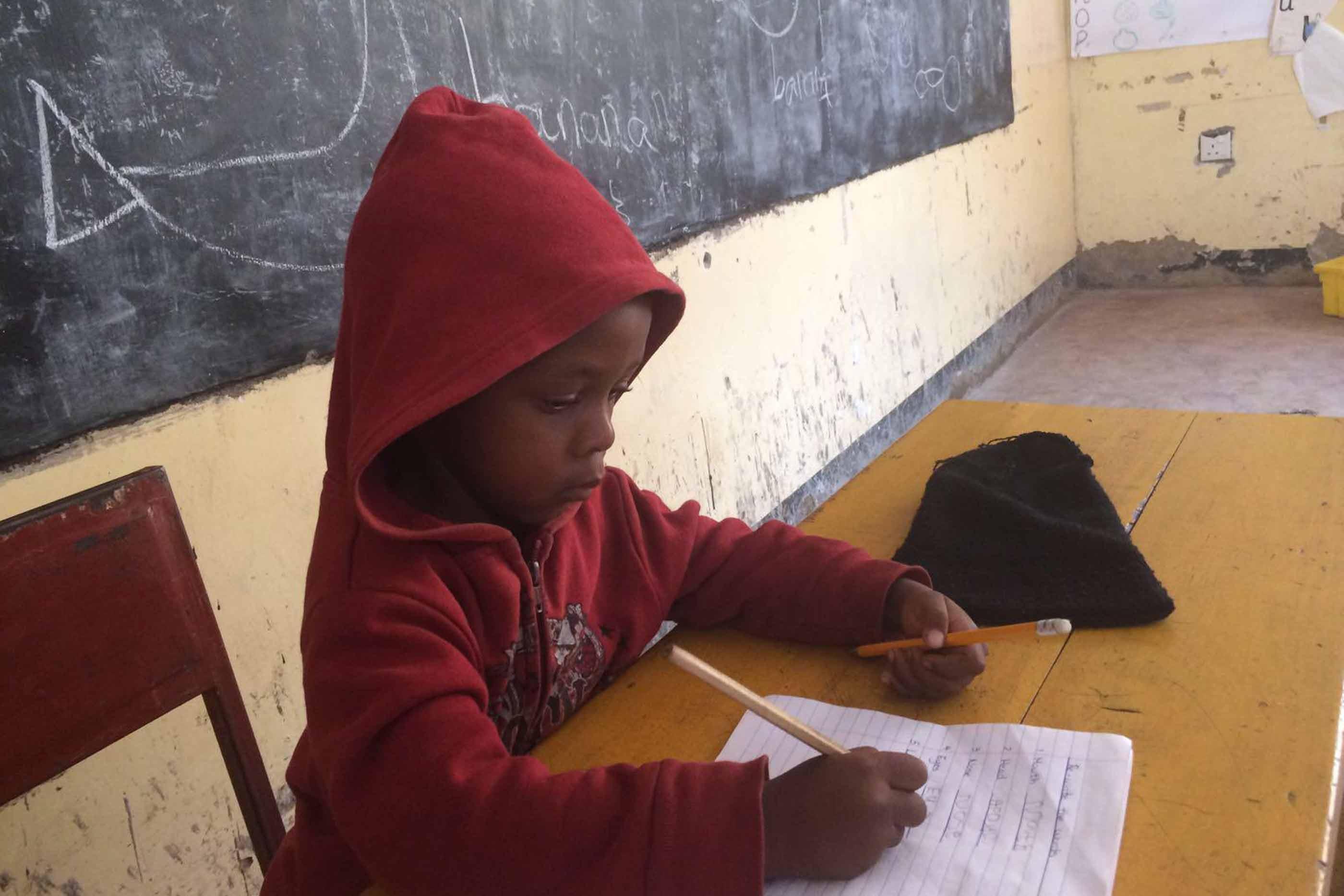 Criança da Tanzânia a aprender a escrever.