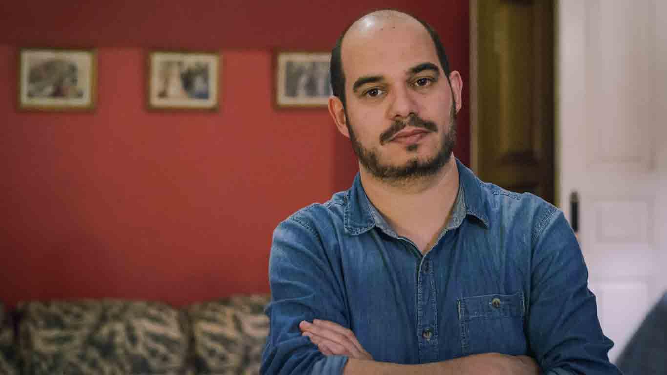João Afonso, CEO e Head of Curation do Gig Club, em primeiro plano, de braços cruzados, num ambiente informal
