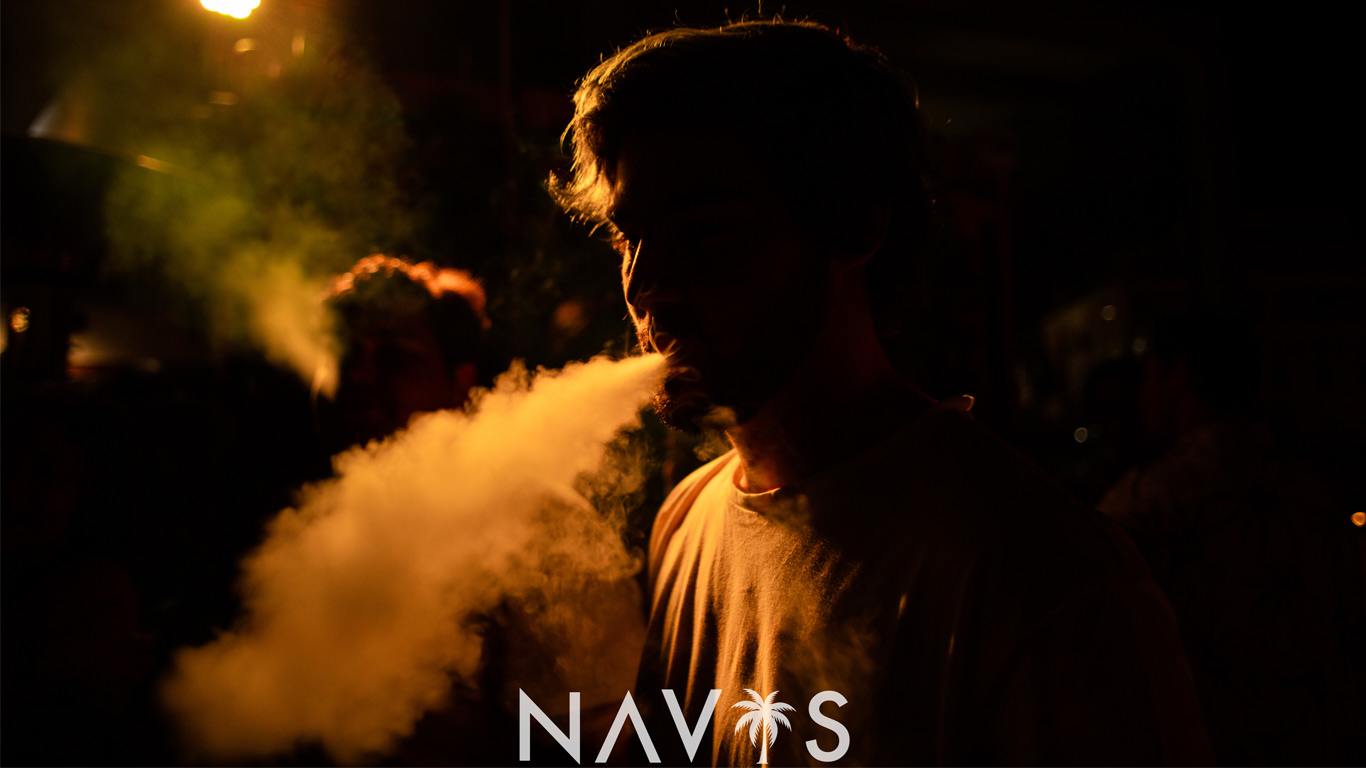 Fotografia de um jovem a fumar um cigarro durante a festa.
