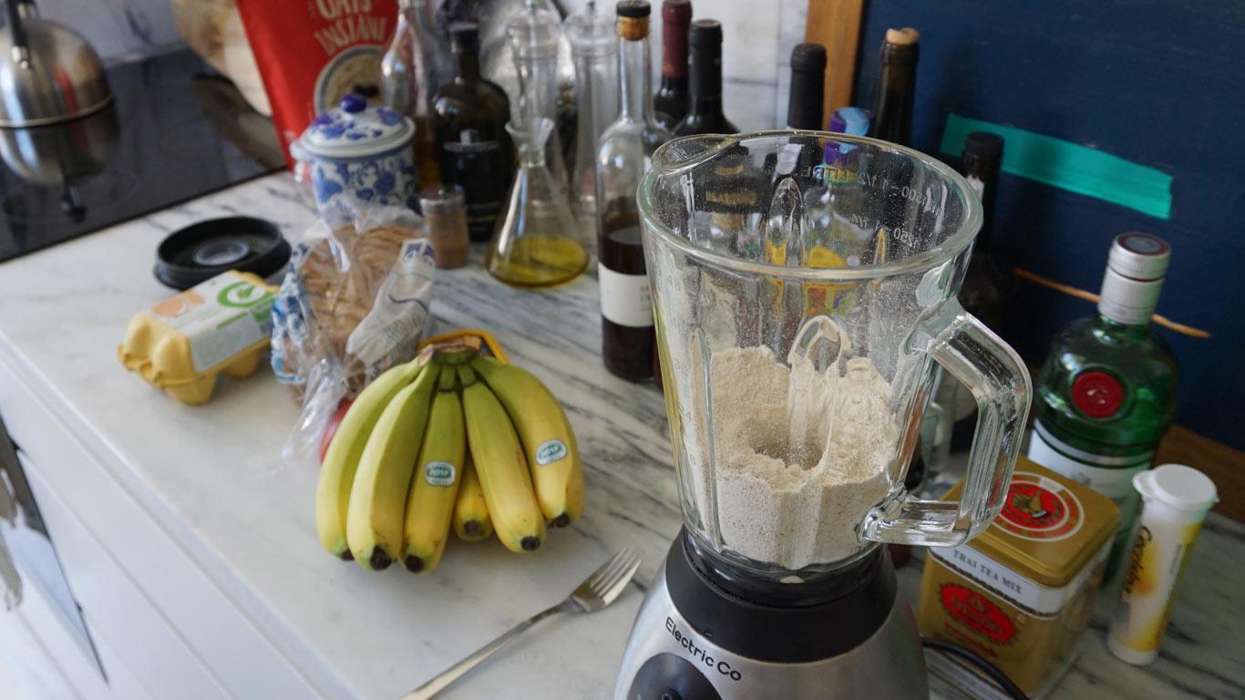 Imagem de um cacho de bananas, 1 tomate, um pacote de pão de forma, uma caixa de ovos e uma liquidificara. plano visto de cima.