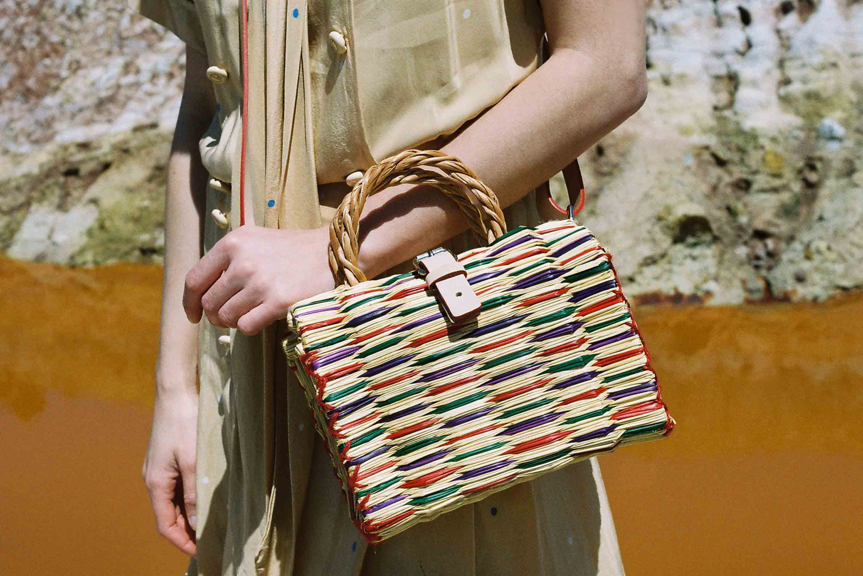 """Modelo a segurar a mala """"Mini"""", tendo como pano de fundo uma pedreira. Um dos artigos da marca TOINO ABEL, feito de junco e vime, com um padrão tingido a azul, vermelho e verde"""
