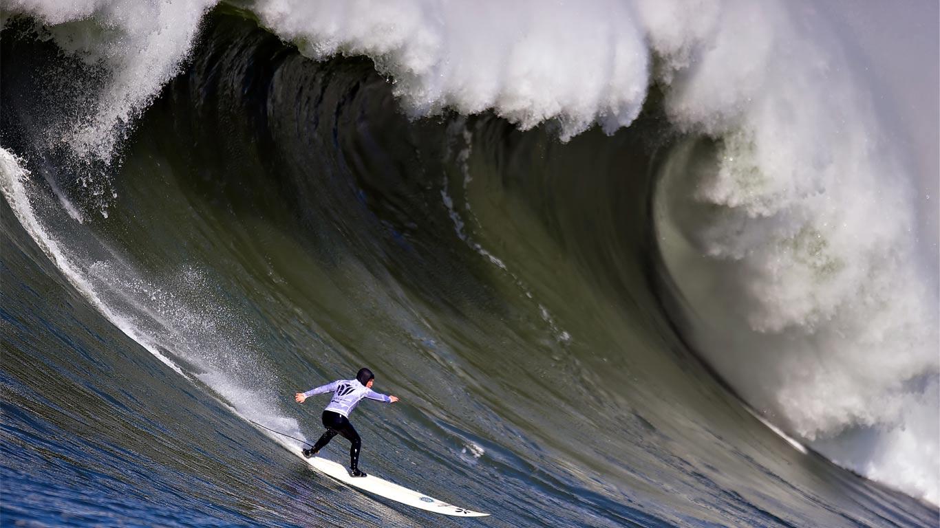 Surfista a surfar uma onda enorme.